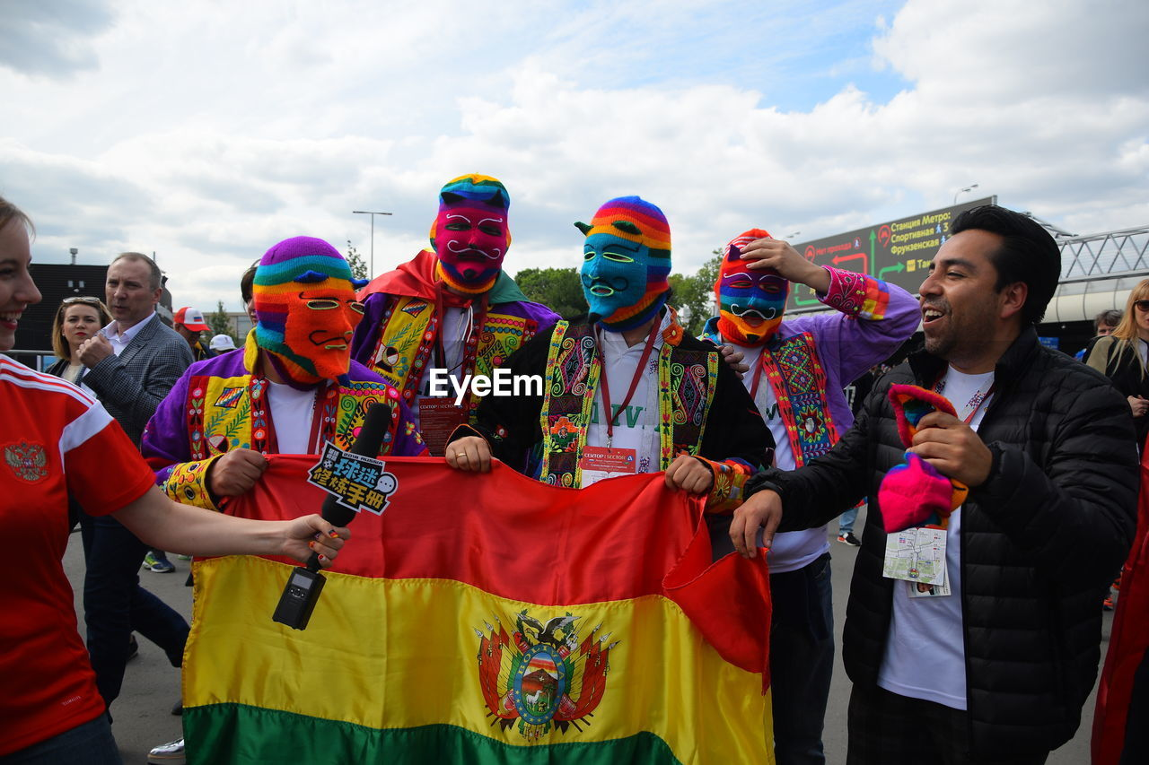 real people, group of people, men, lifestyles, day, cloud - sky, multi colored, celebration, standing, leisure activity, front view, sky, costume, women, people, adult, clothing, outdoors, enjoyment, festival