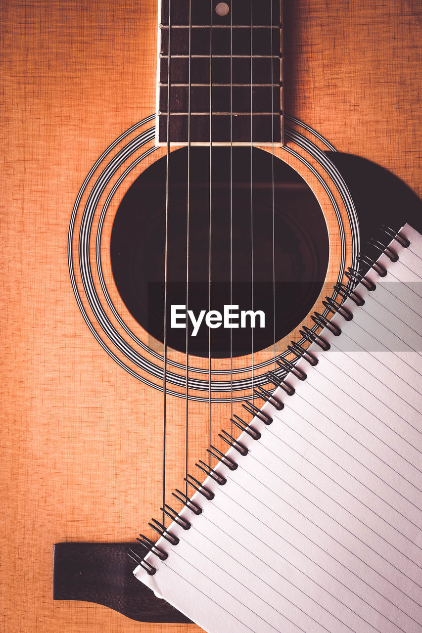 musical instrument, music, musical equipment, string instrument, arts culture and entertainment, no people, musical instrument string, indoors, guitar, string, acoustic guitar, brown, pattern, close-up, wood - material, still life, paper, spiral, piano, high angle view