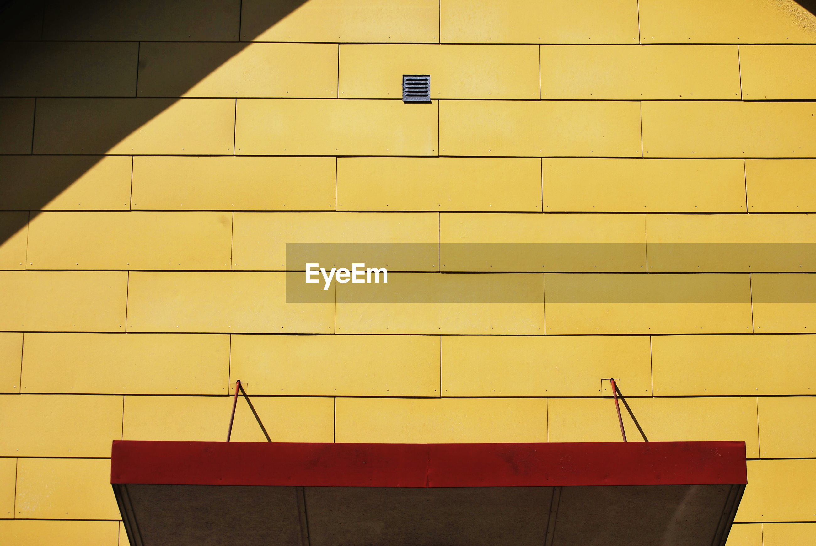 Low angle view of yellow wall against building