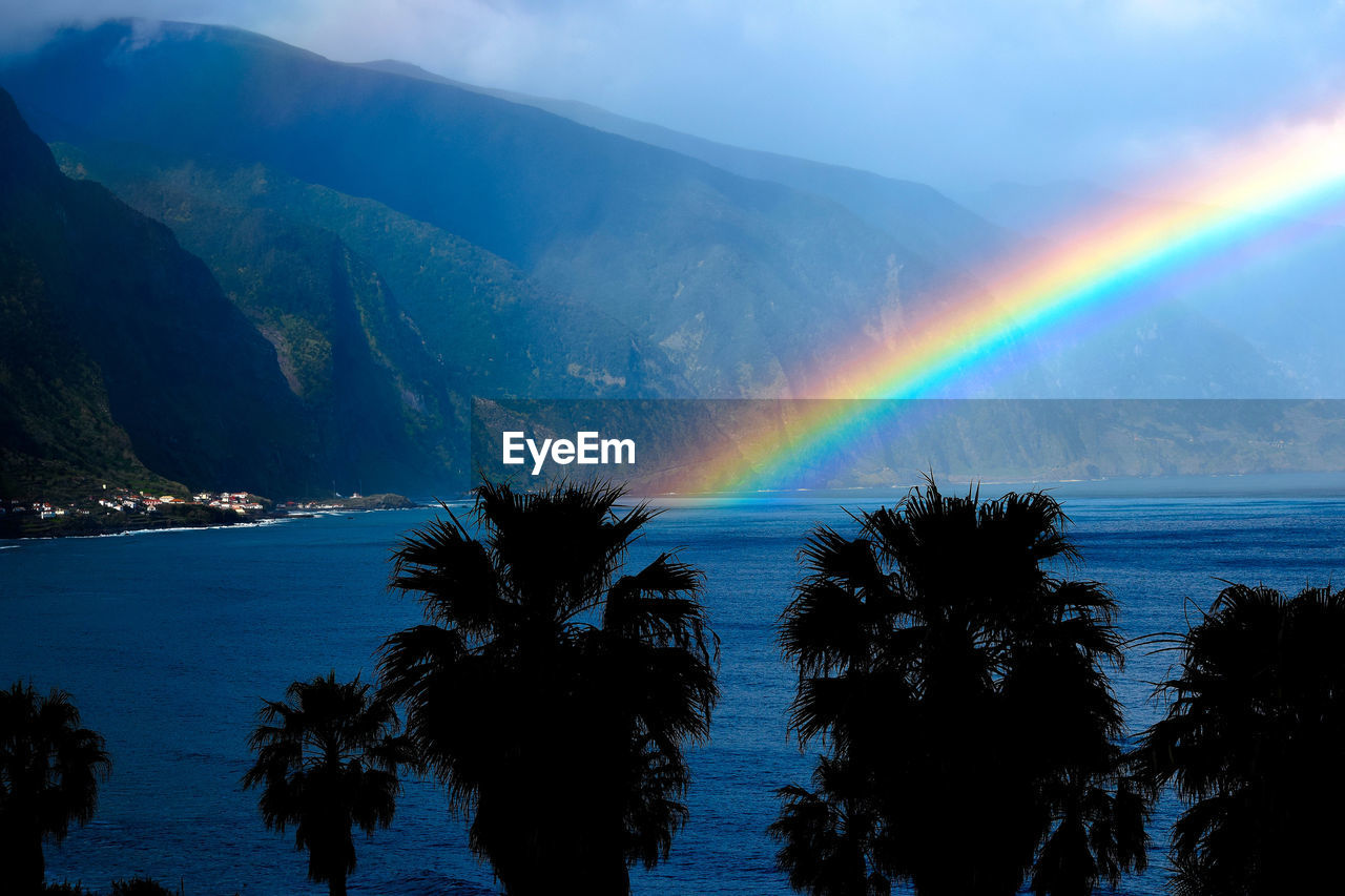 beauty in nature, rainbow, scenics - nature, sky, tranquility, tranquil scene, idyllic, tree, mountain, water, nature, plant, multi colored, non-urban scene, no people, cloud - sky, sea, double rainbow, outdoors