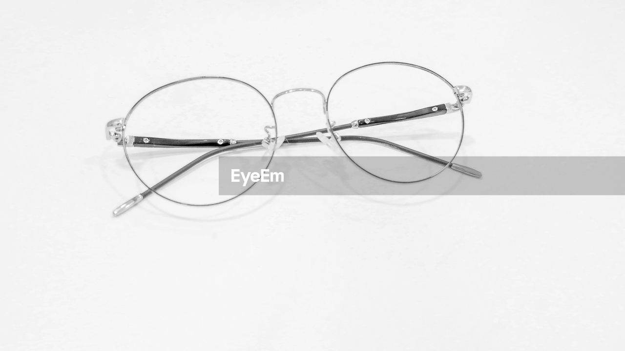 HIGH ANGLE VIEW OF EYEGLASSES ON WHITE WALL