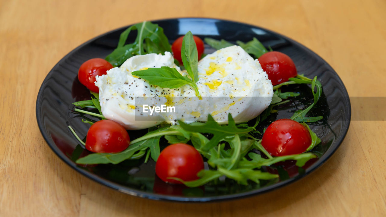 food and drink, food, fruit, healthy eating, freshness, tomato, vegetable, wellbeing, table, ready-to-eat, plate, close-up, still life, salad, indoors, no people, cherry tomato, dairy product, serving size, red, herb, vegetarian food, garnish, food styling, greek food, arugula