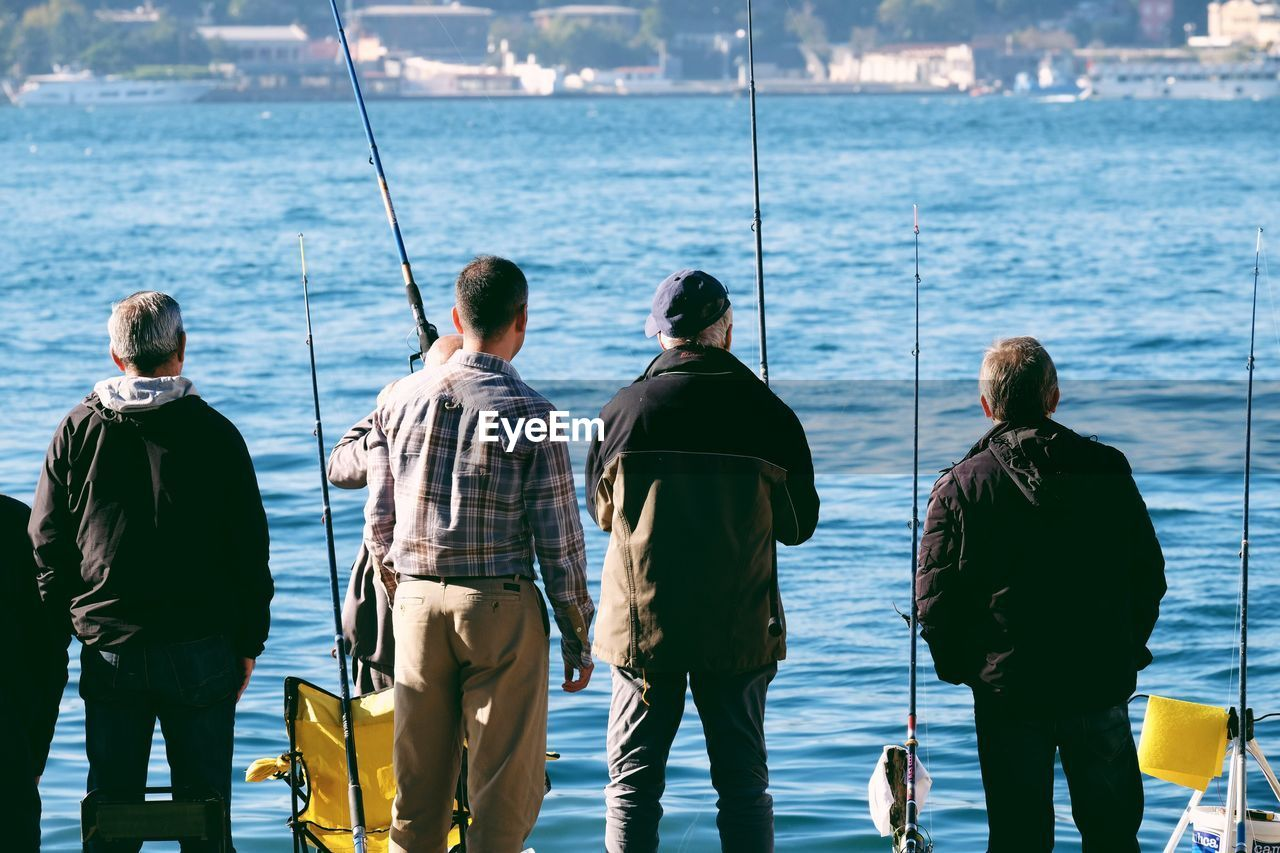 Rear View Of Fishermen Fishing By River