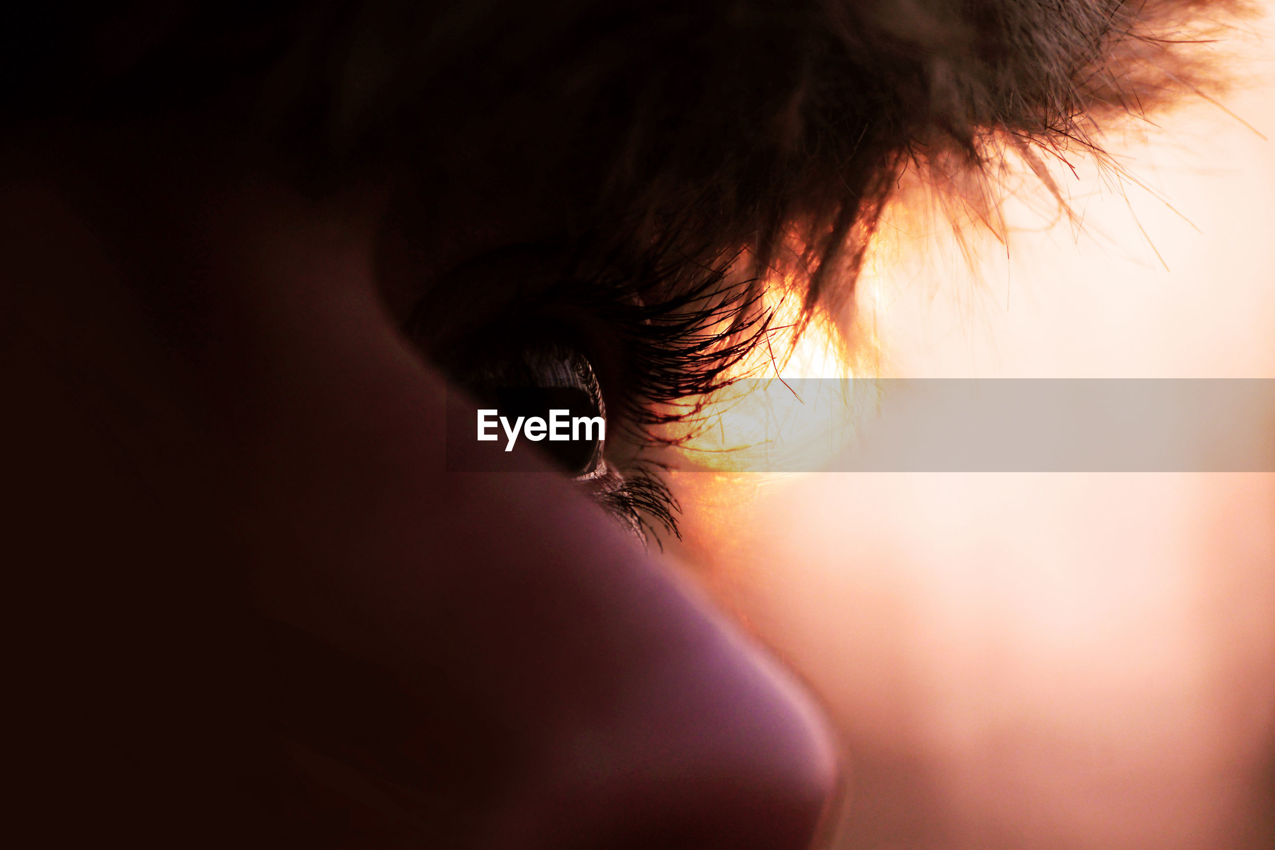 Close-up of woman eye during sunset
