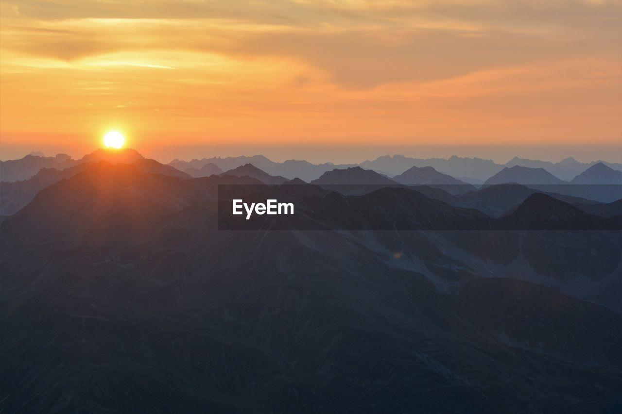sky, sunset, beauty in nature, scenics - nature, mountain, tranquil scene, environment, tranquility, sun, landscape, non-urban scene, idyllic, cloud - sky, orange color, nature, mountain range, no people, sunlight, outdoors, remote, mountain peak