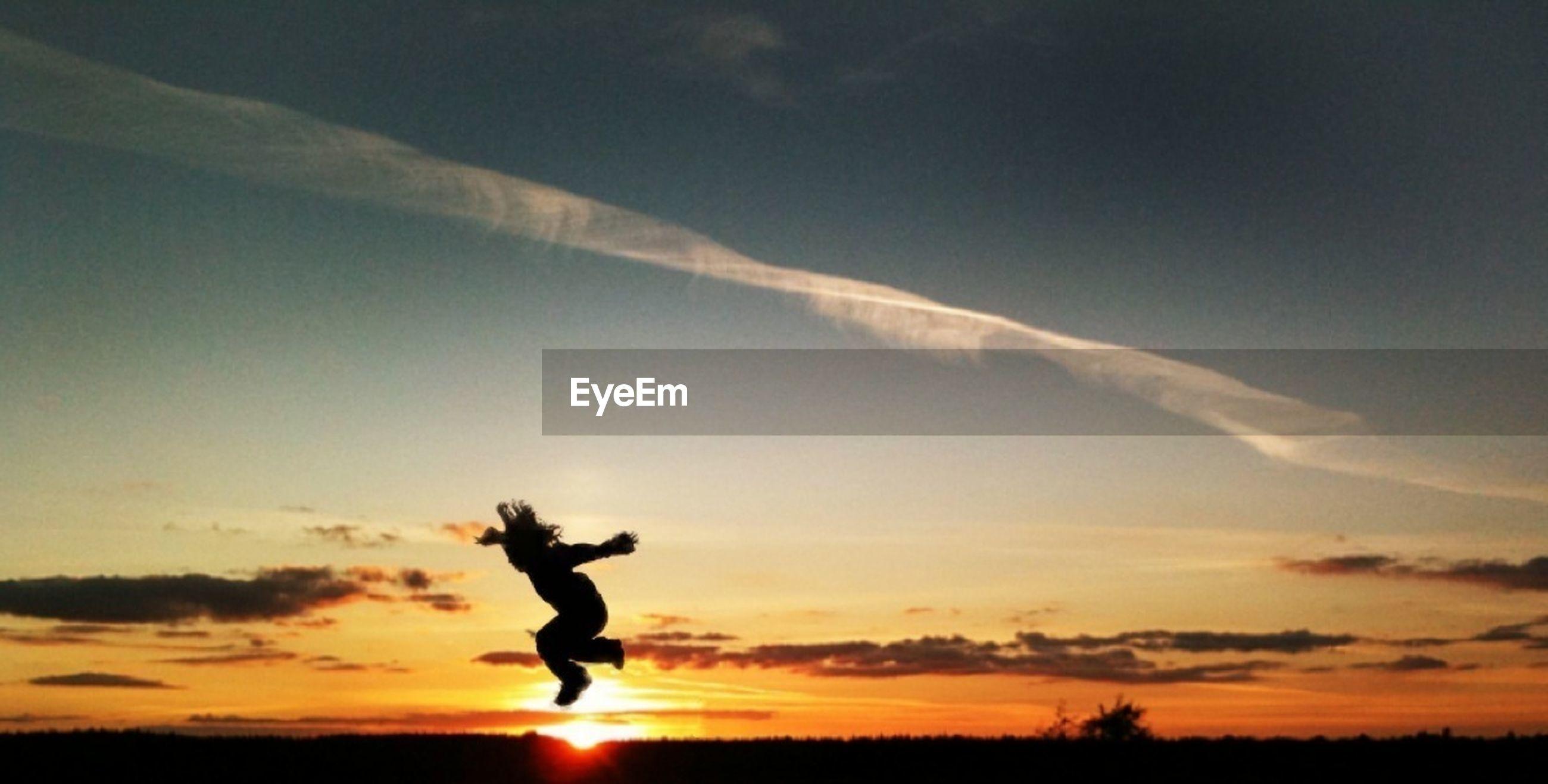 SUN SHINING THROUGH MAN JUMPING IN SKY