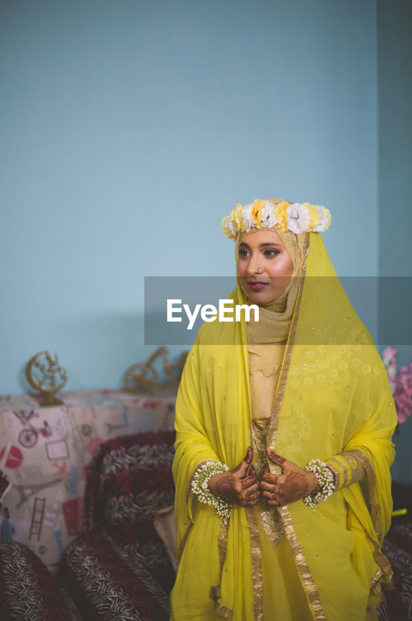Bride Wearing Traditional Clothing Looking Away At Home