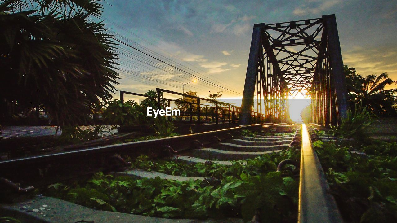 Railroad Track By Bridge Against Cloudy Sky During Sunset