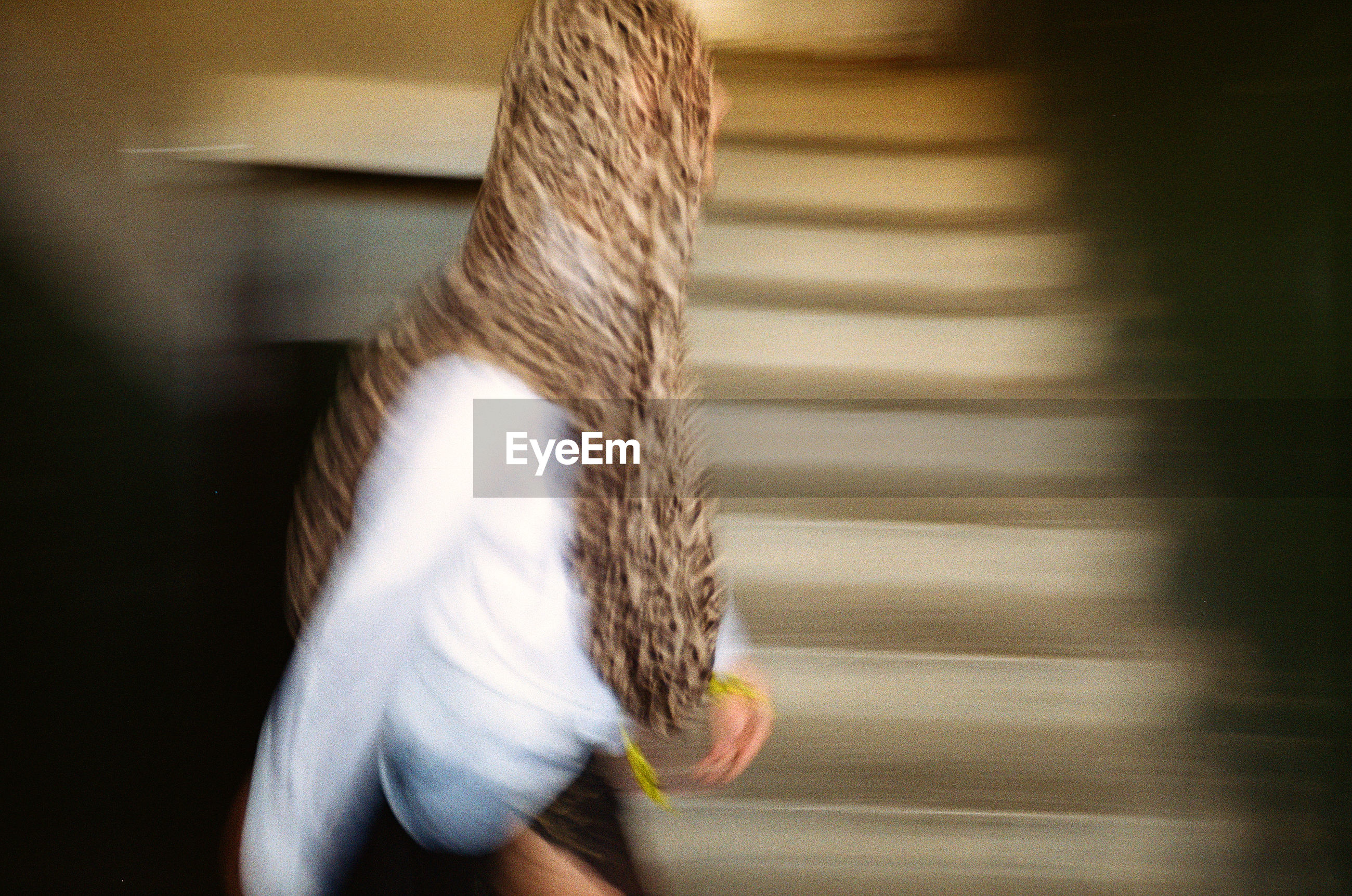 Blurred motion of person walking by staircase