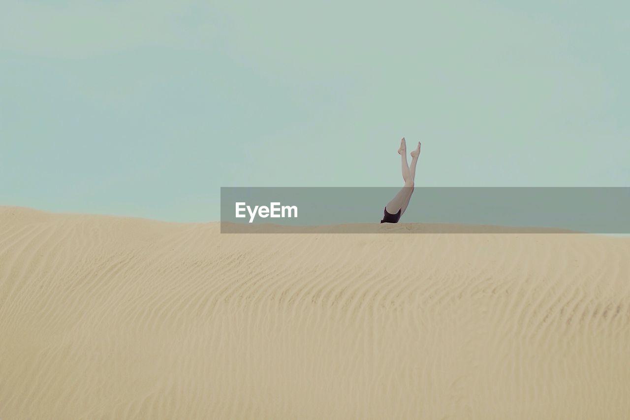 Woman with legs raised on sand dune