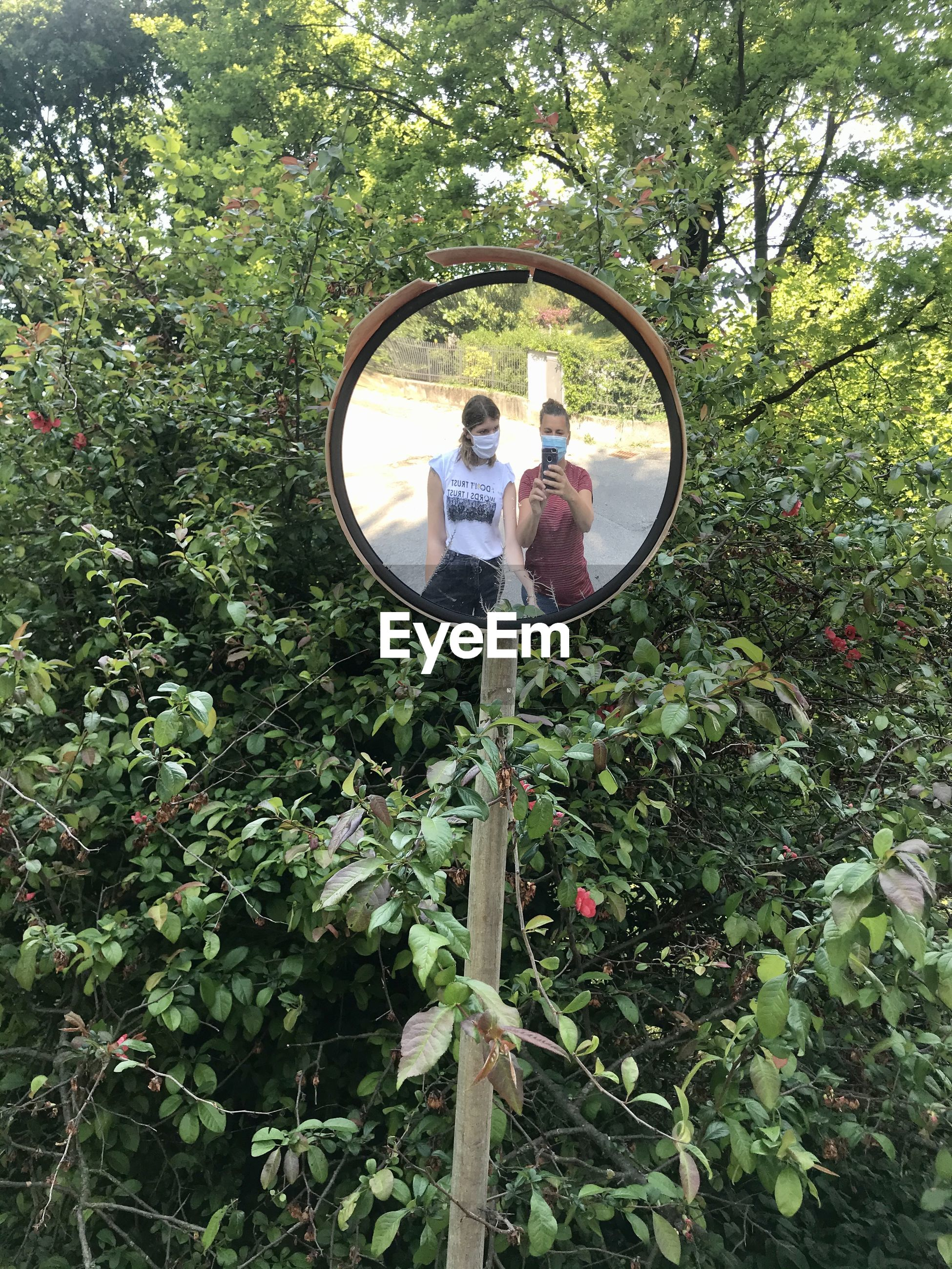 Friends taking selfie reflecting on road mirror in forest
