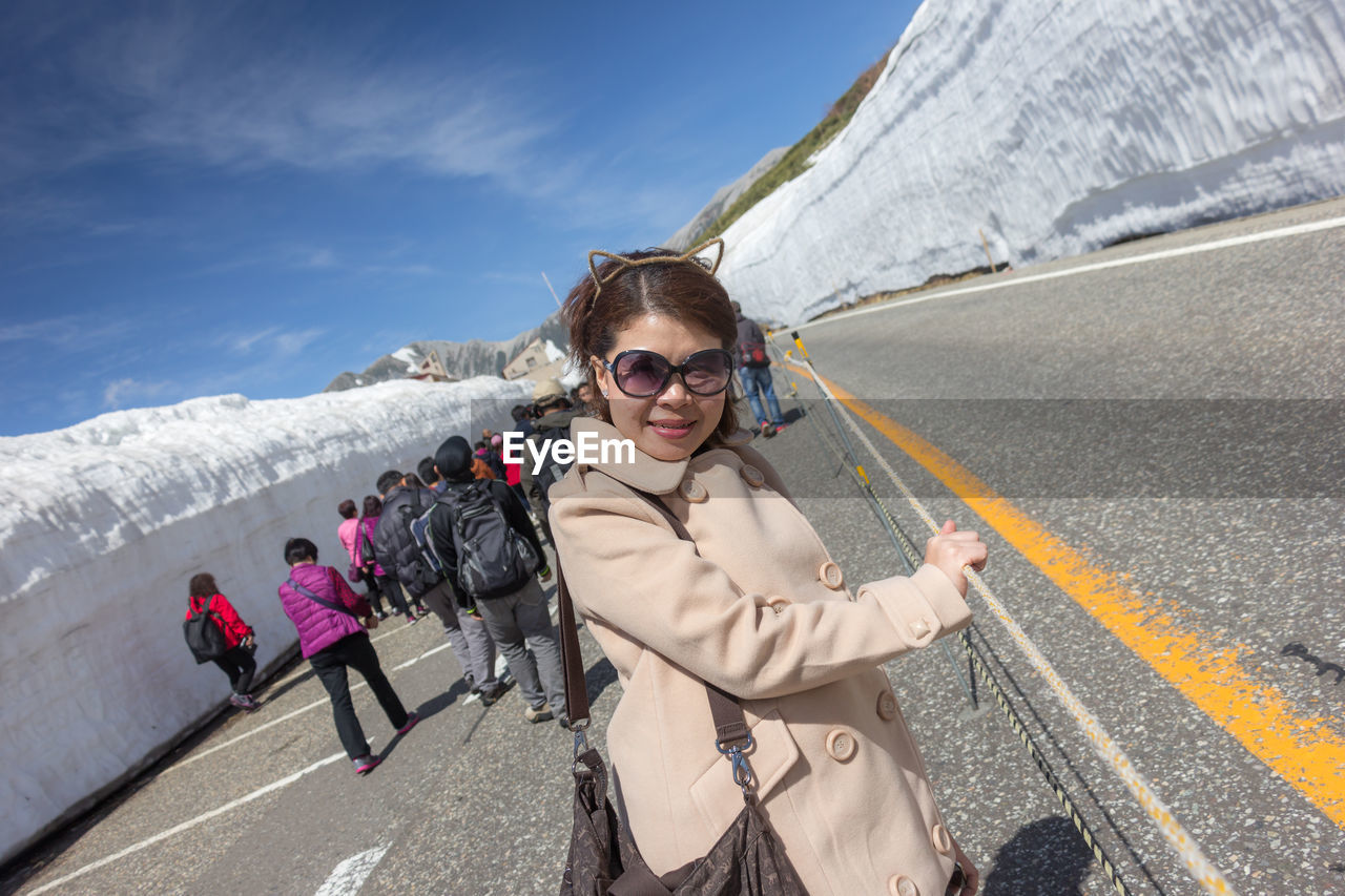 Portrait of woman in sunglasses standing on road during winter