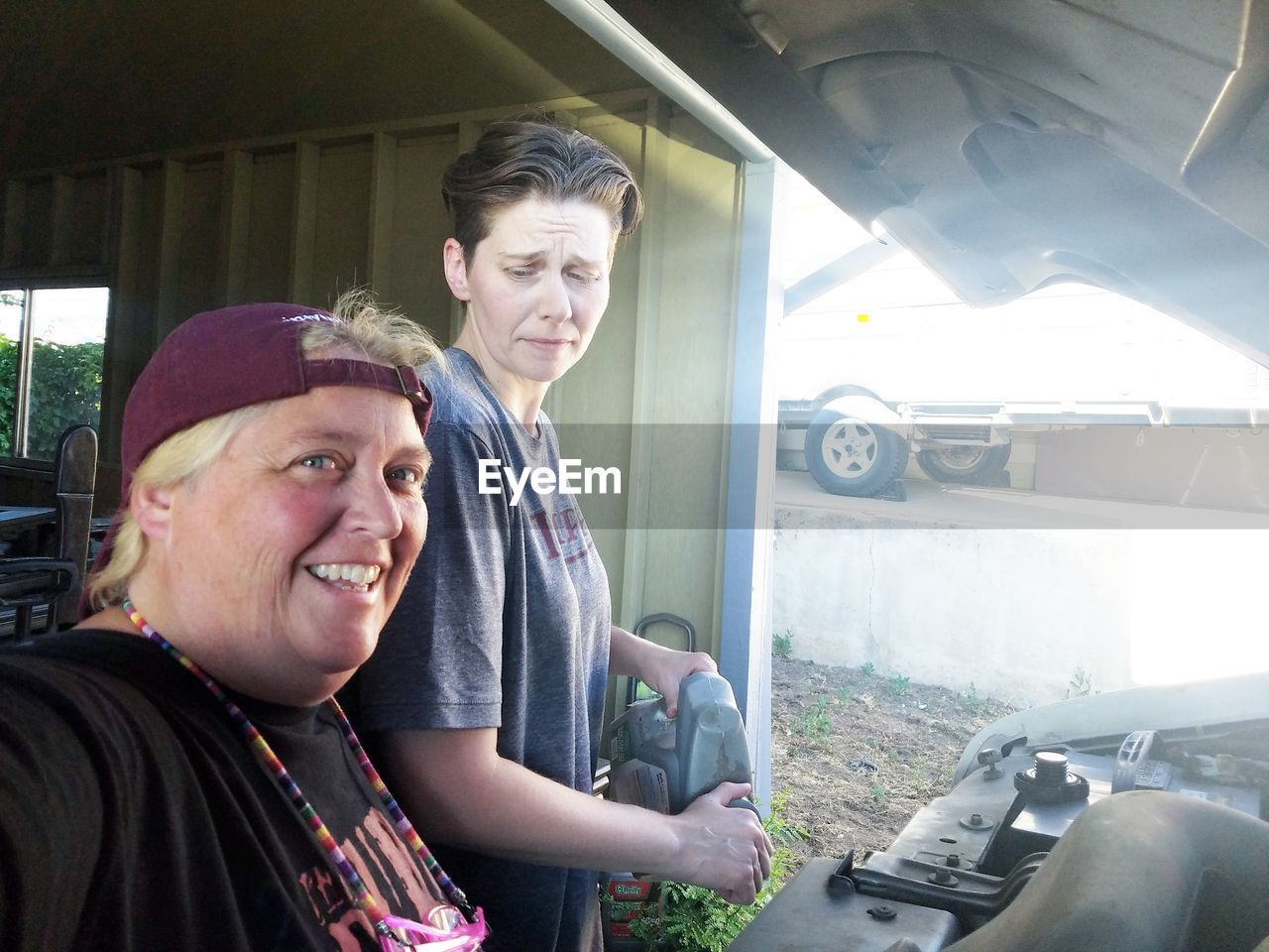 Portrait of mature woman with friend by car at garage