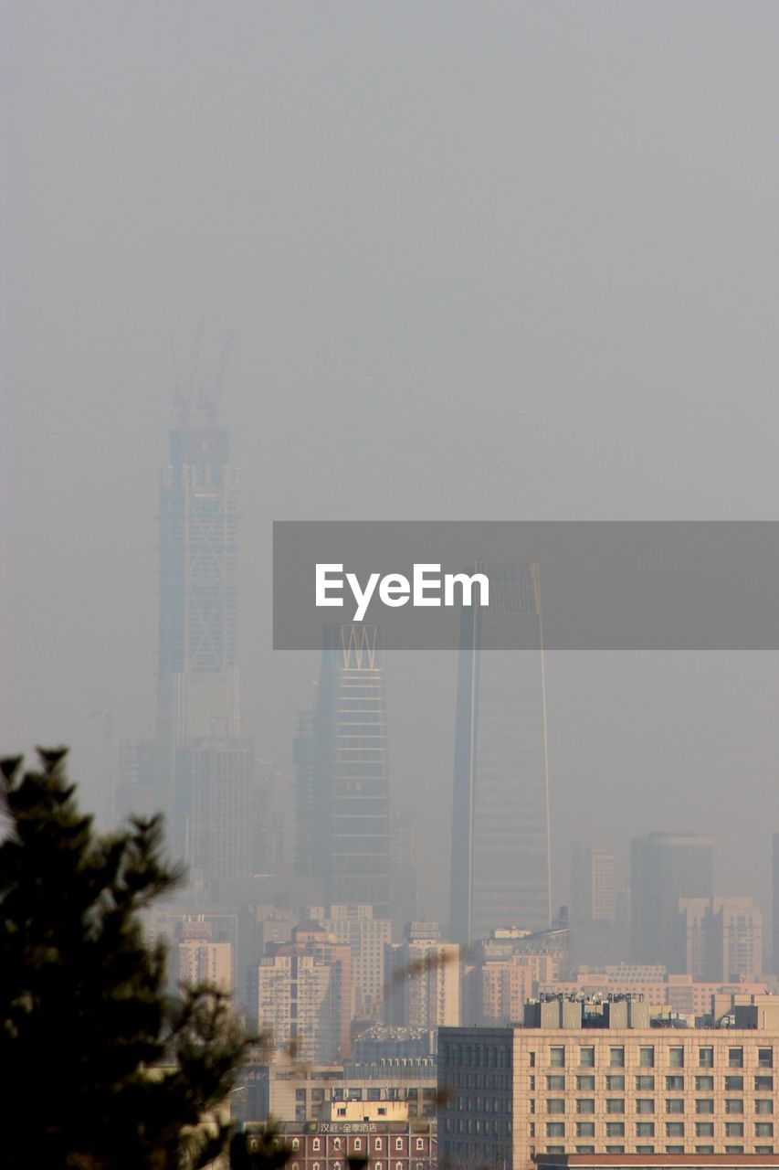 MODERN BUILDINGS IN CITY AGAINST SKY DURING FOGGY WEATHER