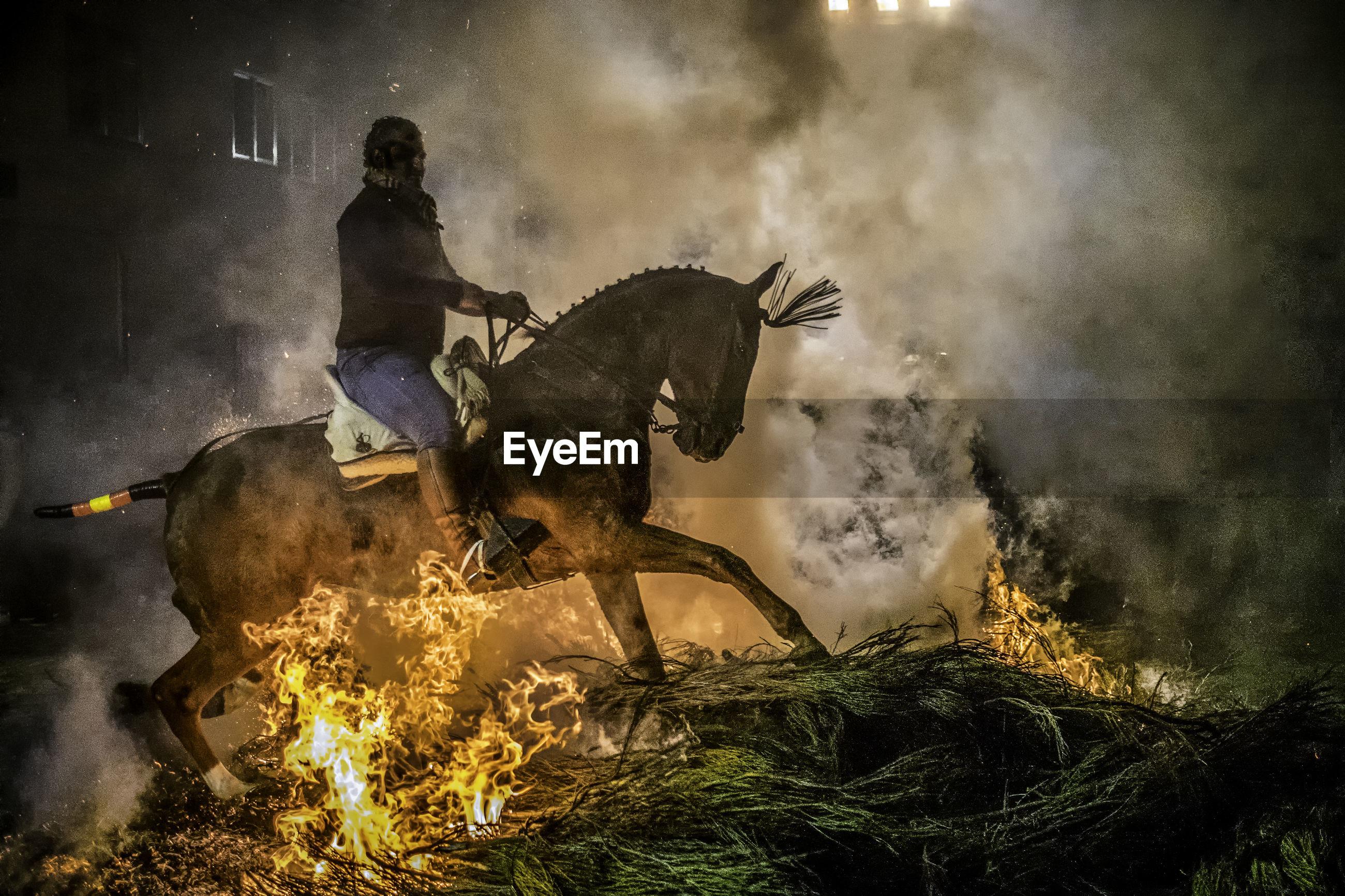 MEN STANDING AGAINST FIRE ON NIGHT
