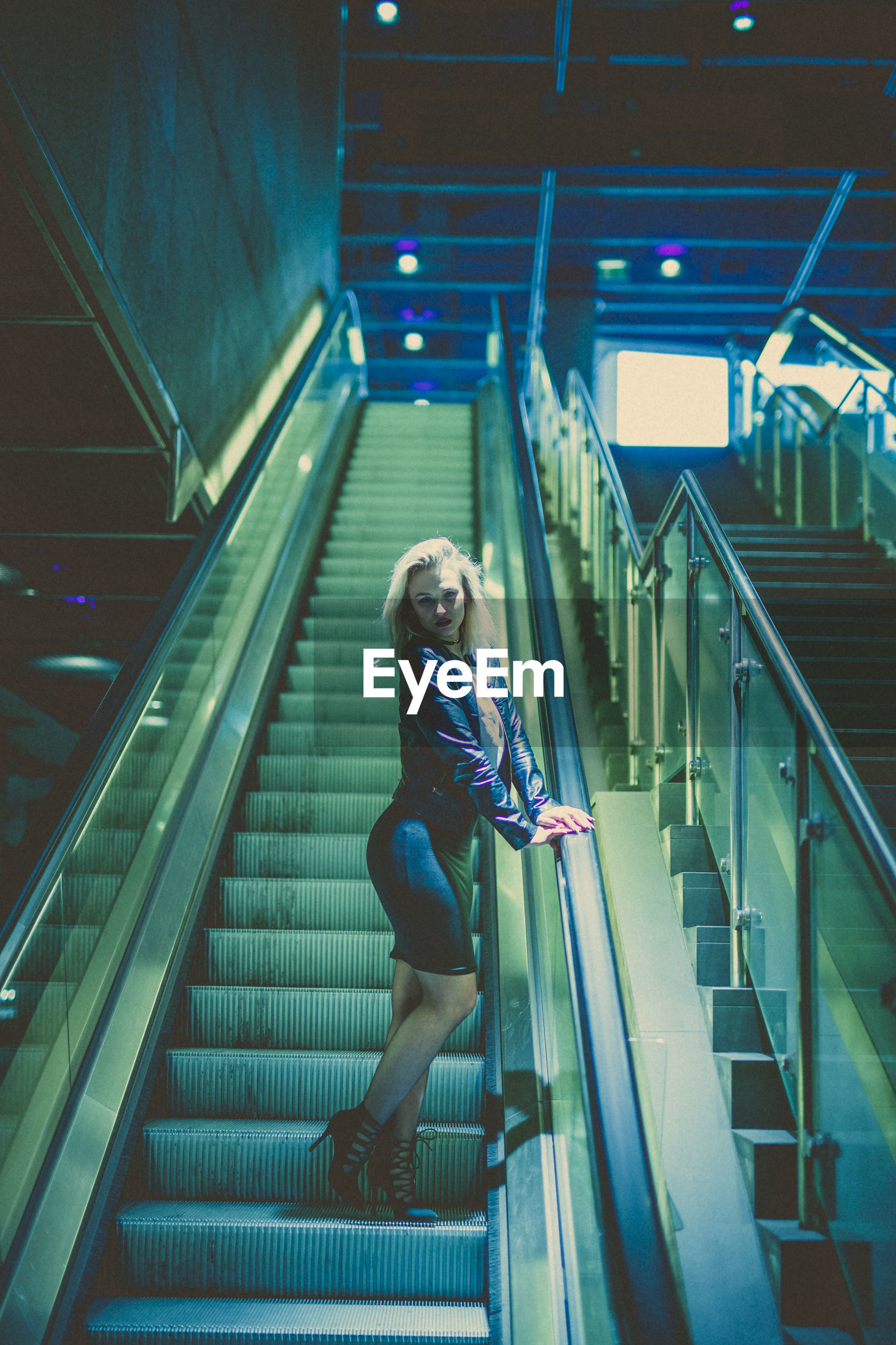 Low angle view of young woman standing on escalator