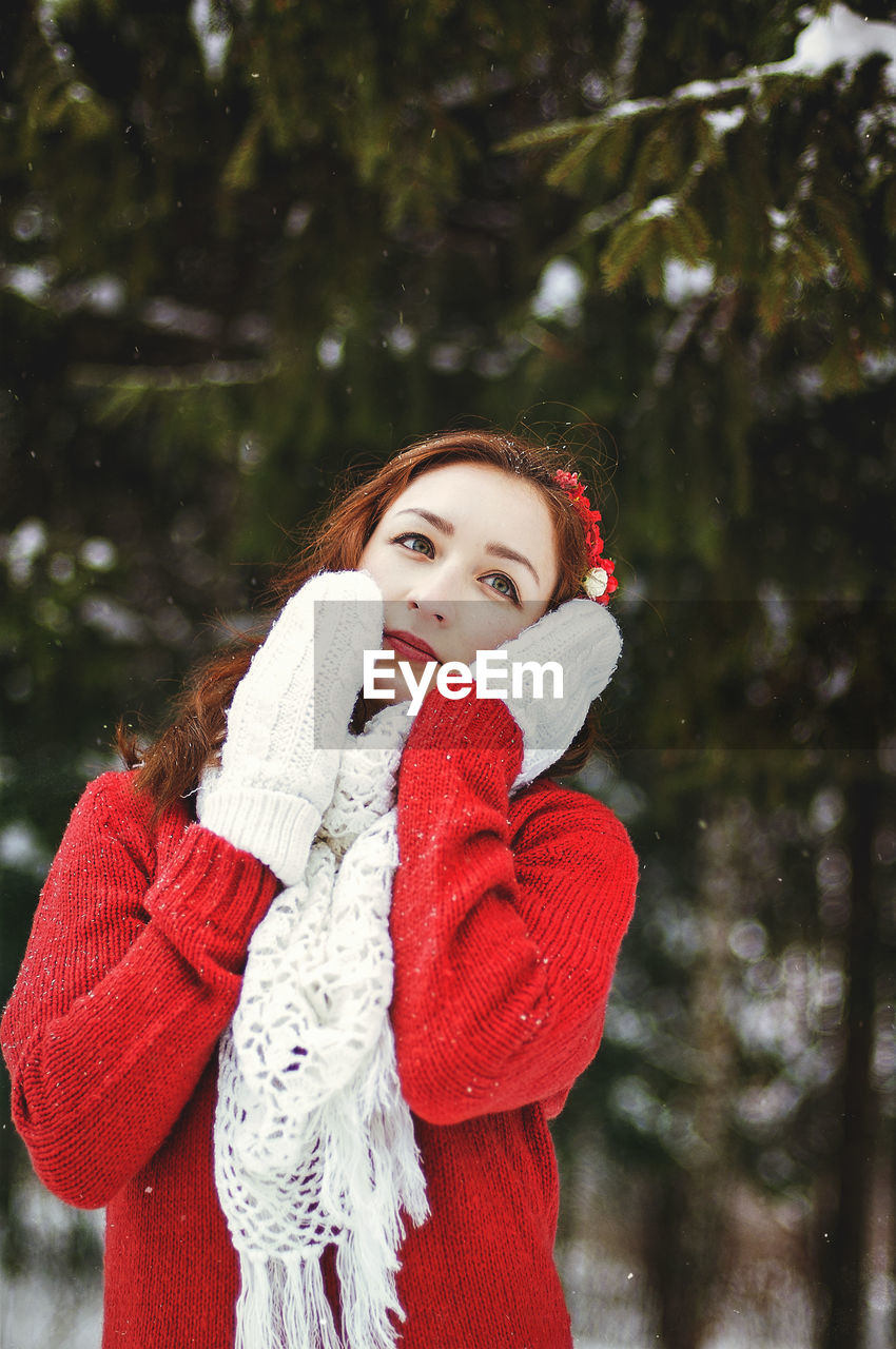 Redhead beautiful woman in red sweater and white gloves walking in the frozen winter forest.