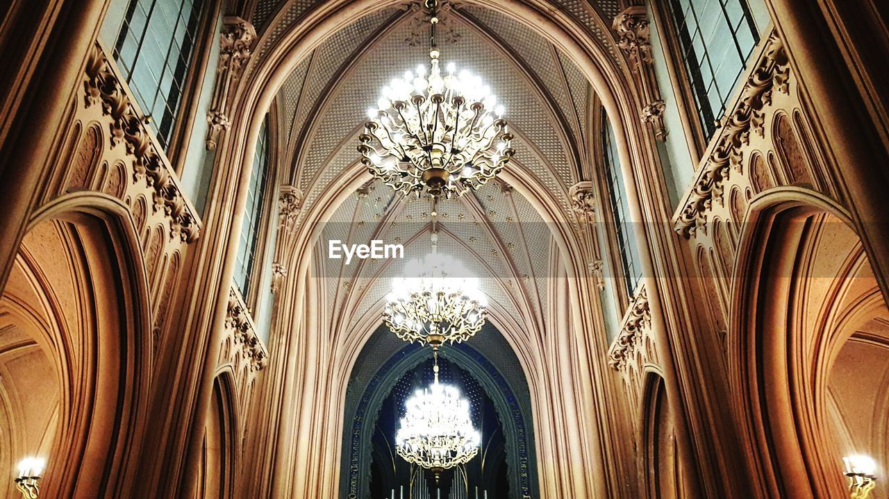 ceiling, architecture, indoors, arch, low angle view, place of worship, religion, no people, hanging, history, built structure, day