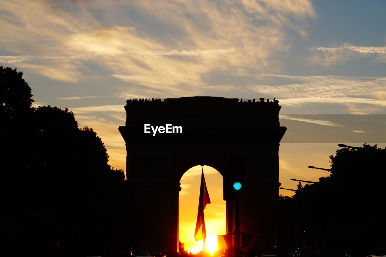 SILHOUETTE OF CITY AGAINST SKY AT SUNSET