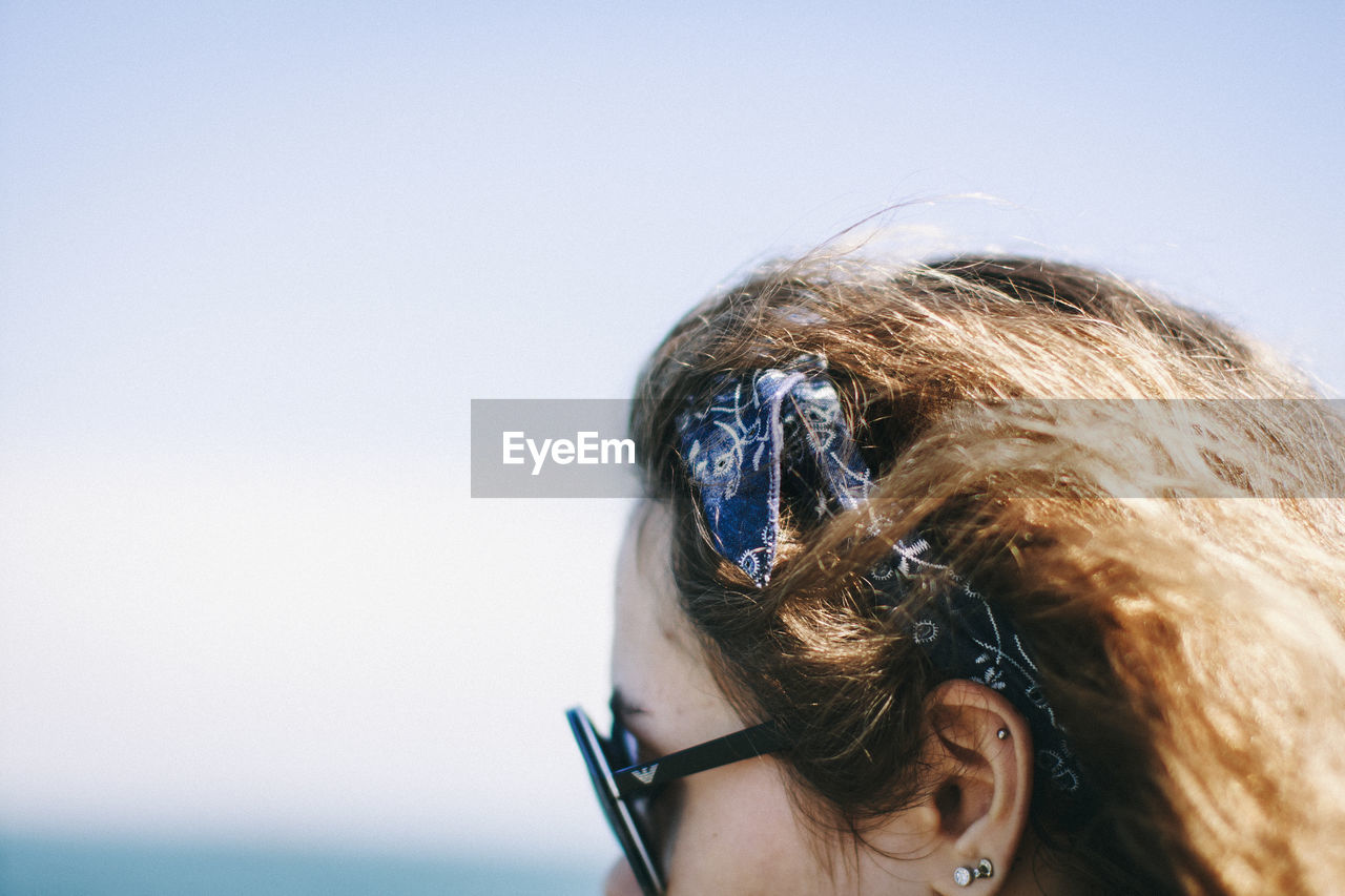 Cropped Image Of Woman With Brown Hair Wearing Headband And Sunglasses Against Sky