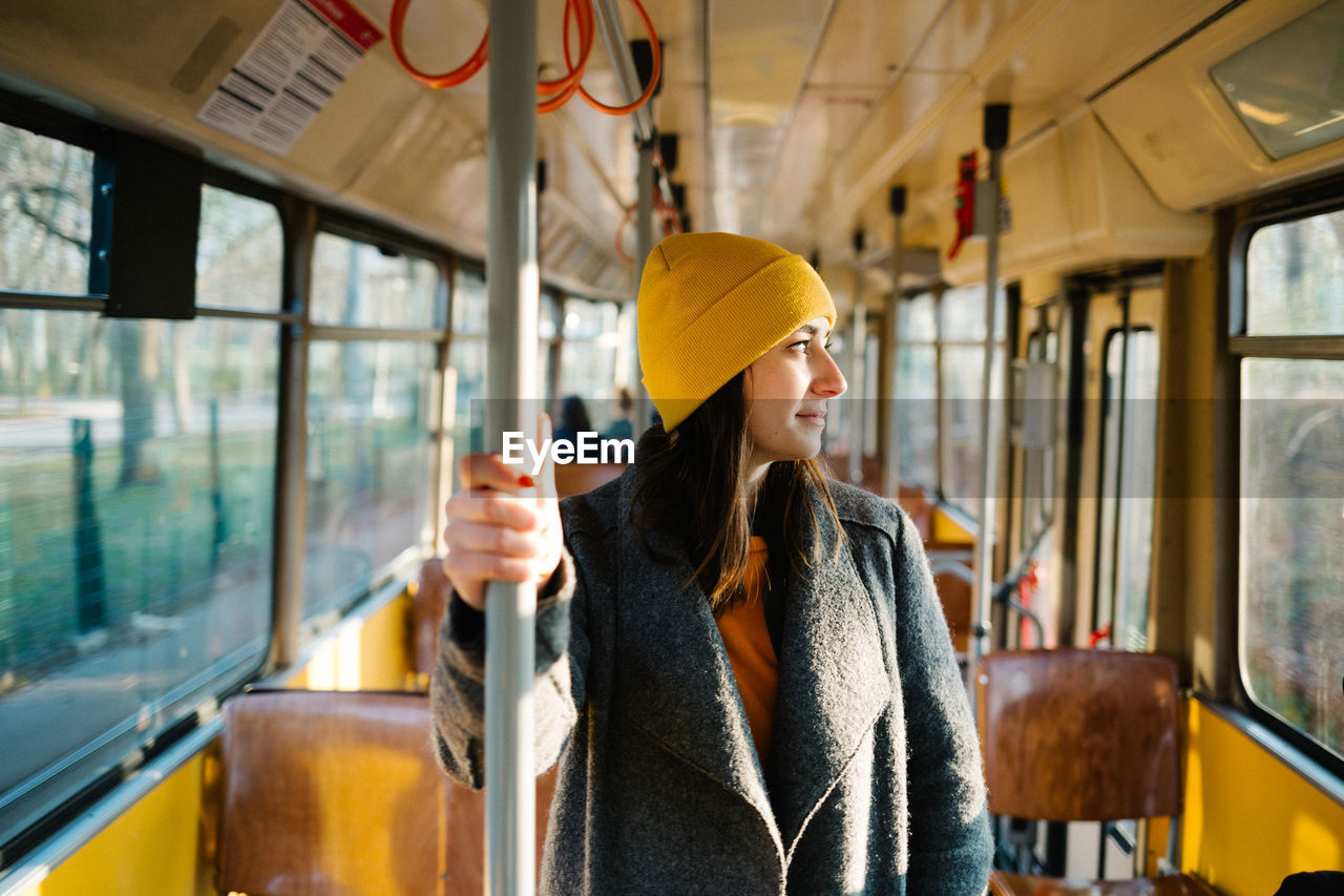 public transportation, one person, rail transportation, mode of transportation, train, train - vehicle, real people, young adult, young women, vehicle interior, transportation, waist up, looking away, window, looking, bus, day, lifestyles, warm clothing, outdoors