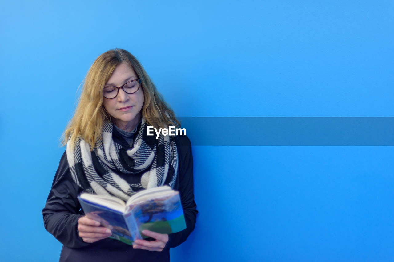 Woman reading book against blue background