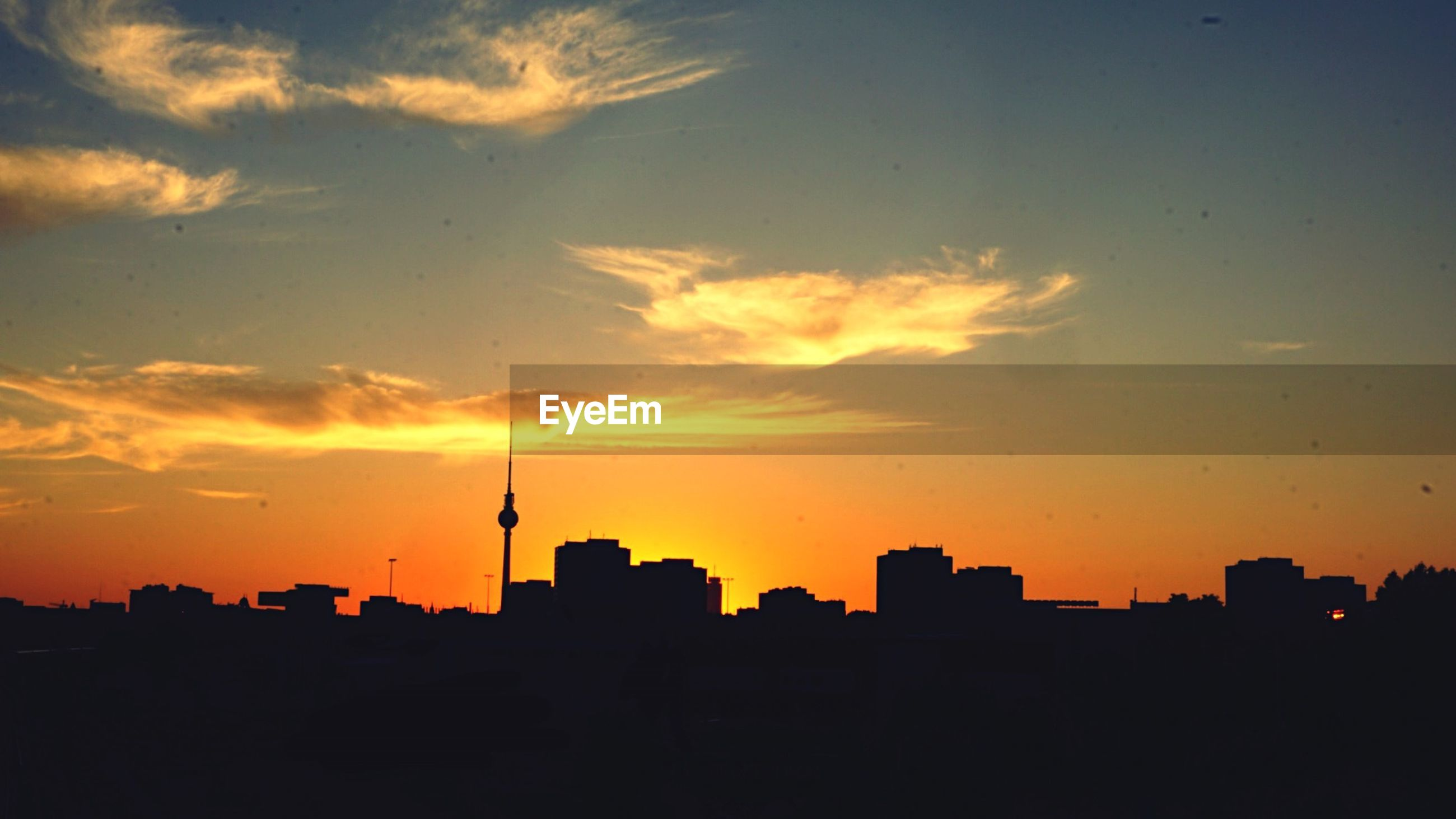 Silhouette city with fernsehturm against orange sky