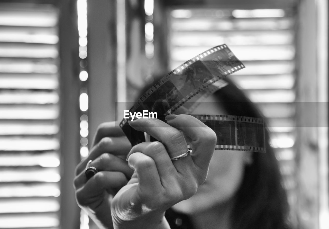 Close-Up Of Woman Looking Film Reel At Home