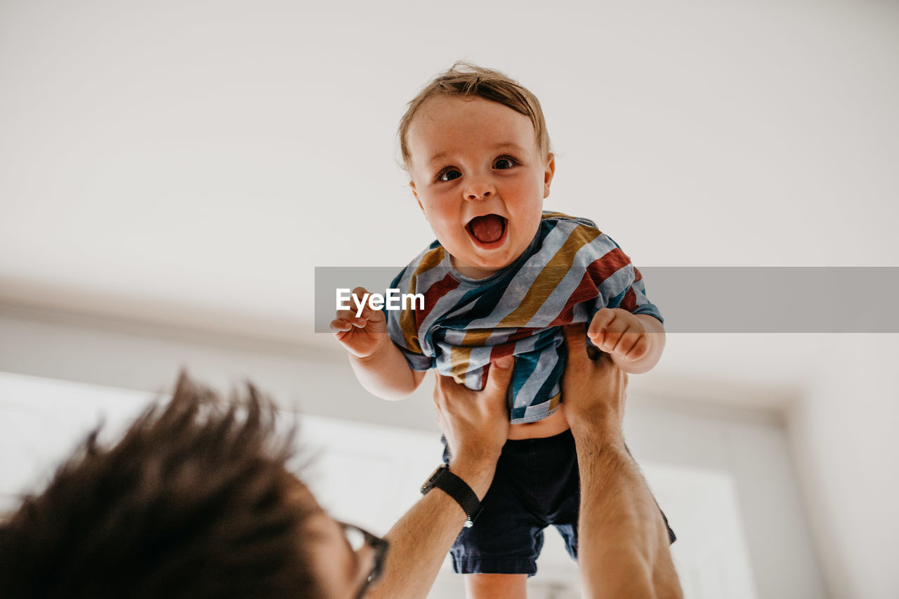 Portrait Of Cheerful Baby Boy Carried By Father At Home