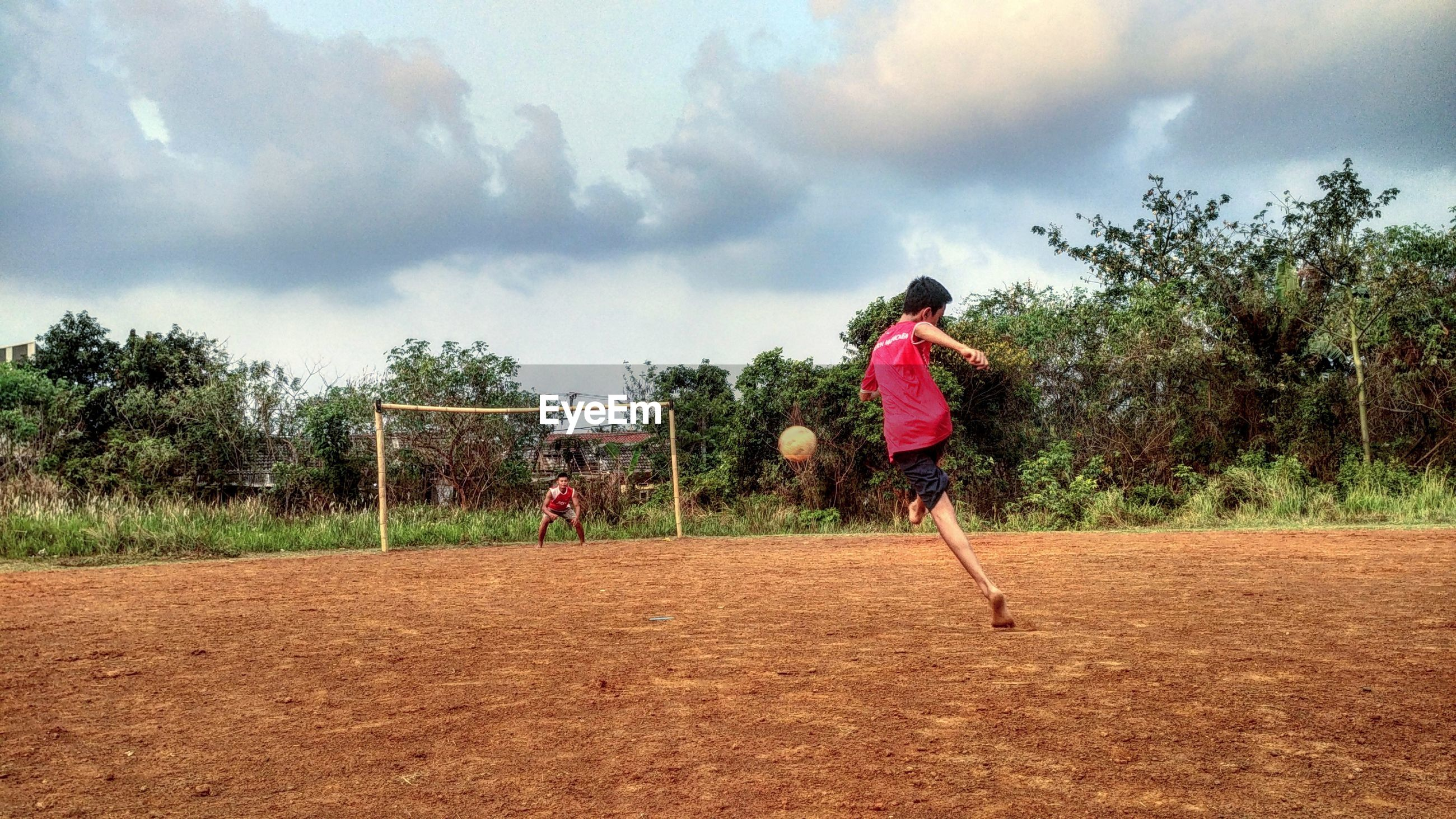 Friends playing soccer on field against sky