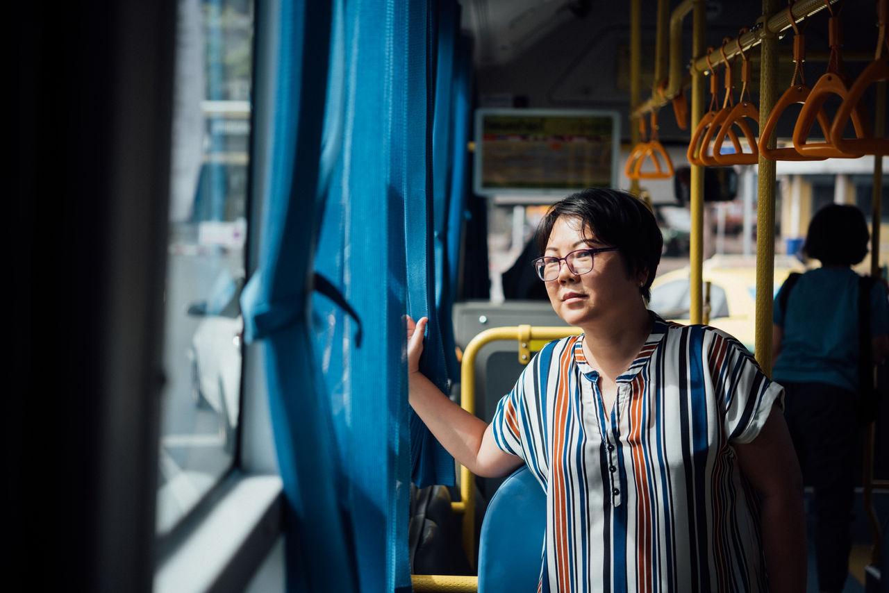 Woman looking through window in bus