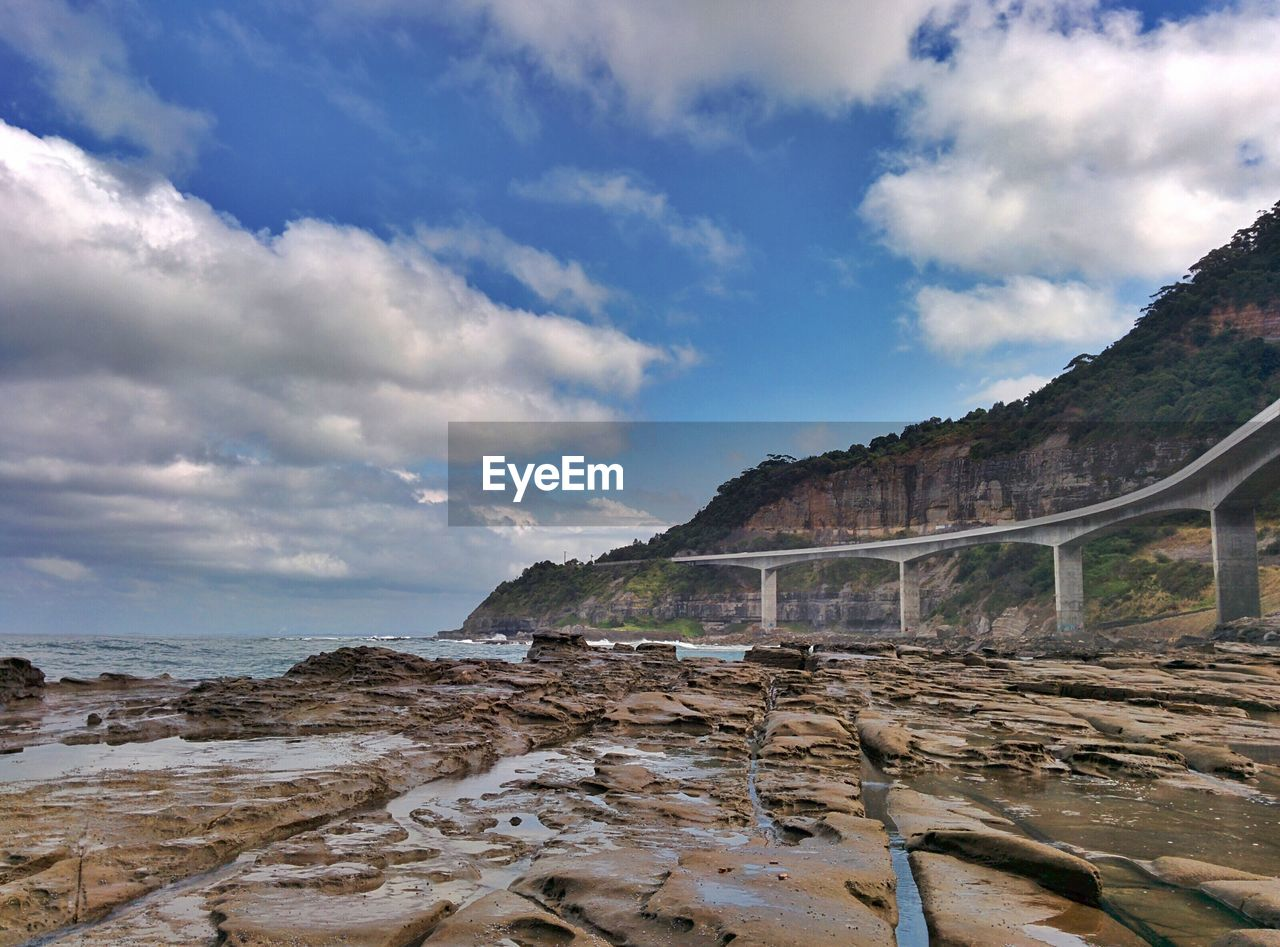 Sea Cliff Bridge By Rocky Mountains Against Cloudy Sky