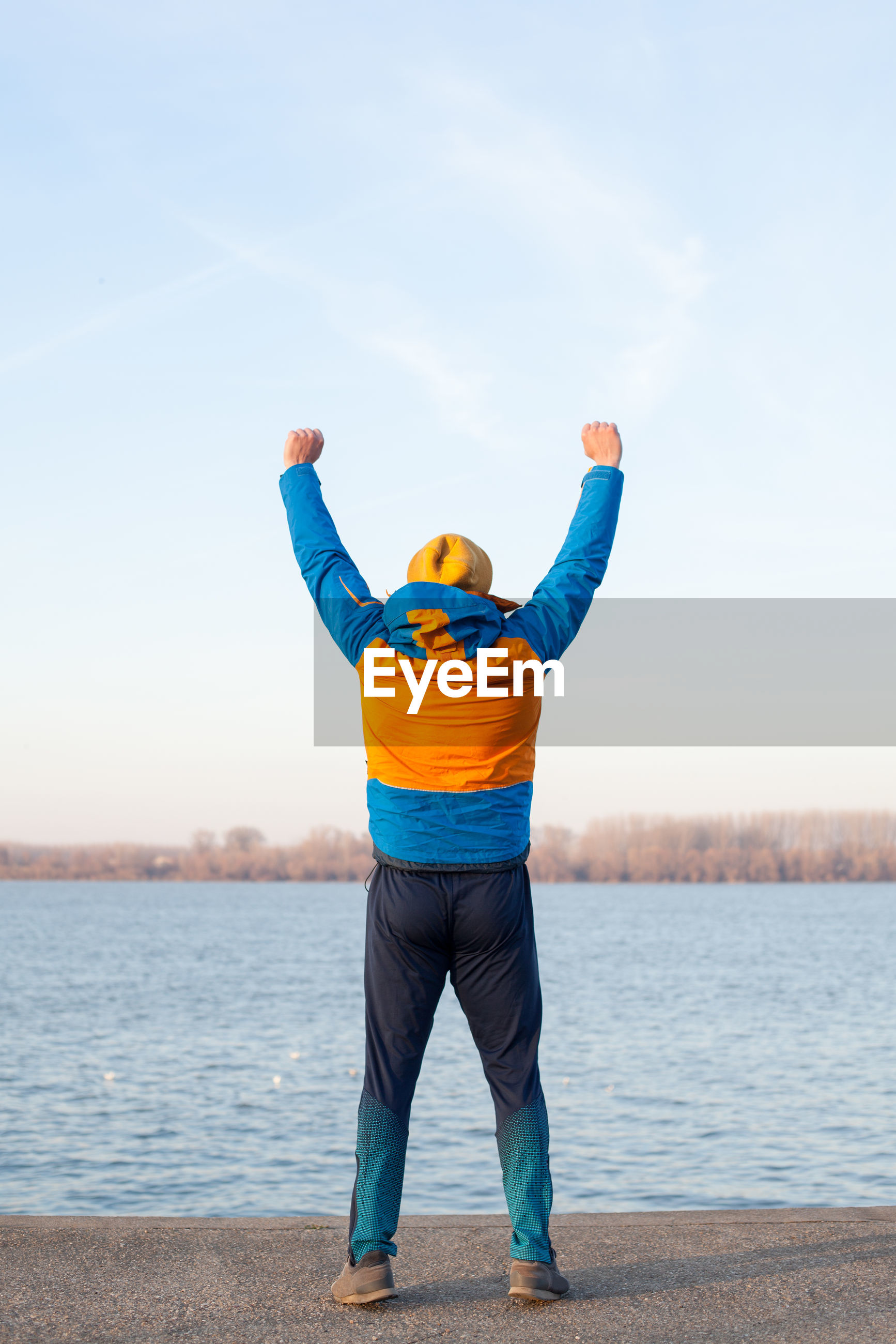Rear view of man with arms raised standing by river
