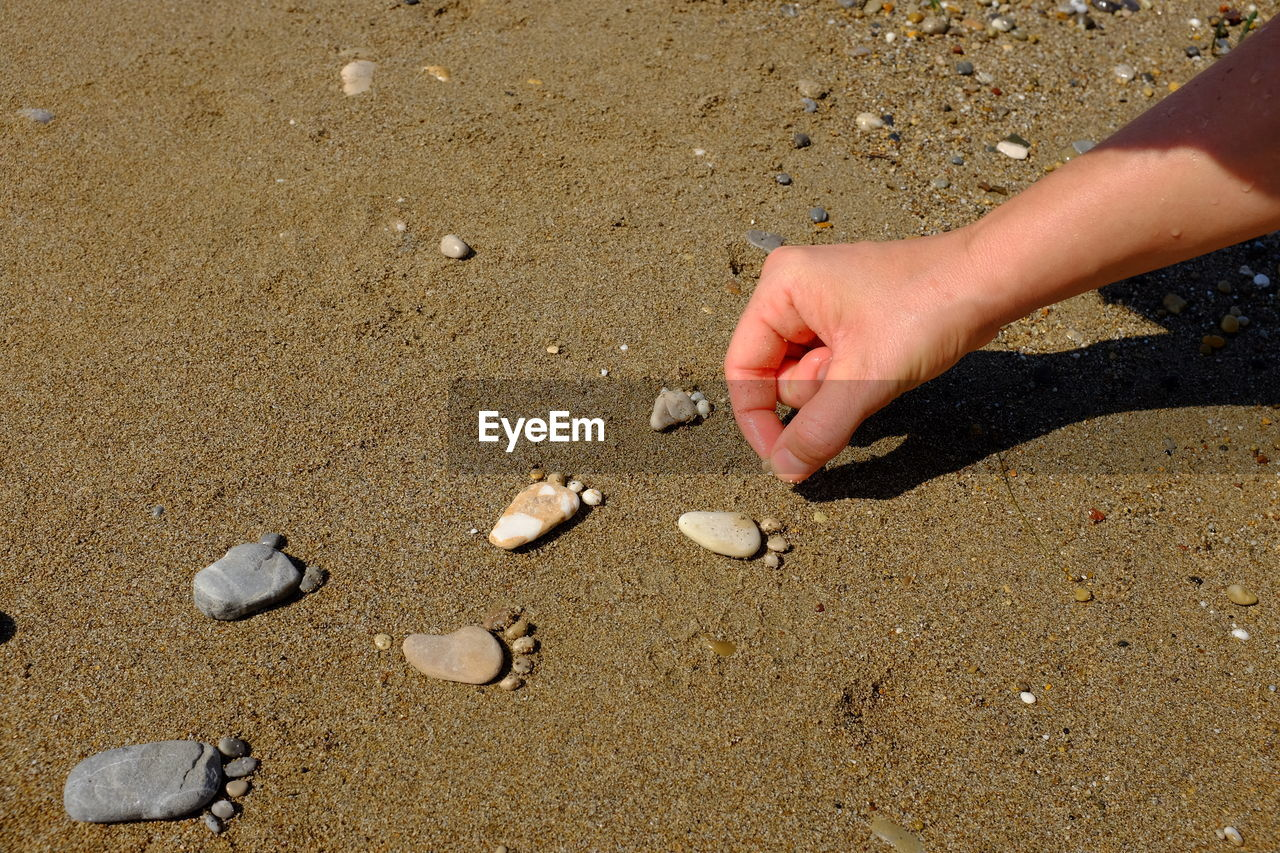 High angle view of hands on arranging pebbles on sand at beach