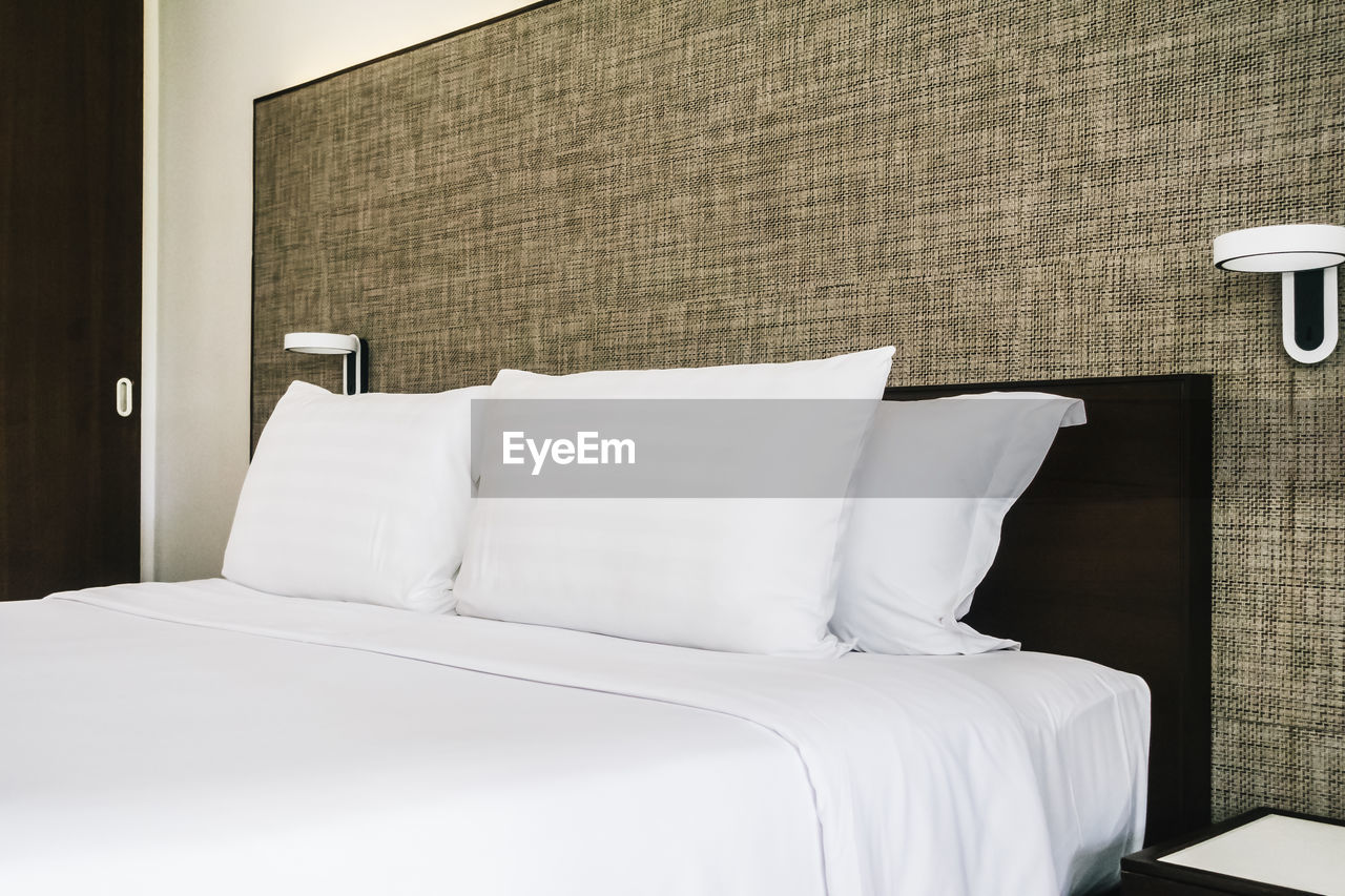 White Bed With Pillows In Bedroom