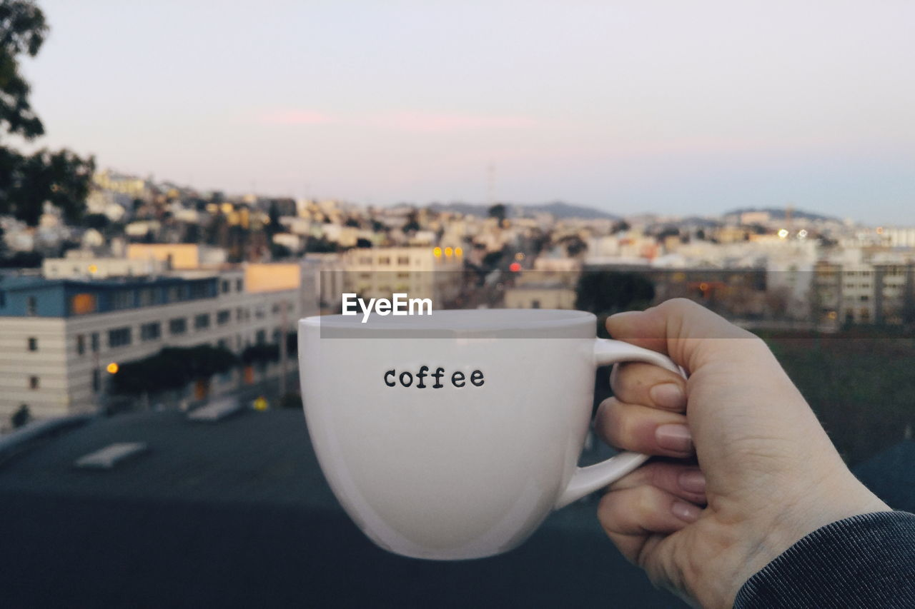 Cropped Image Of Person Holding Coffee Cup With Text On It Against City During Sunset