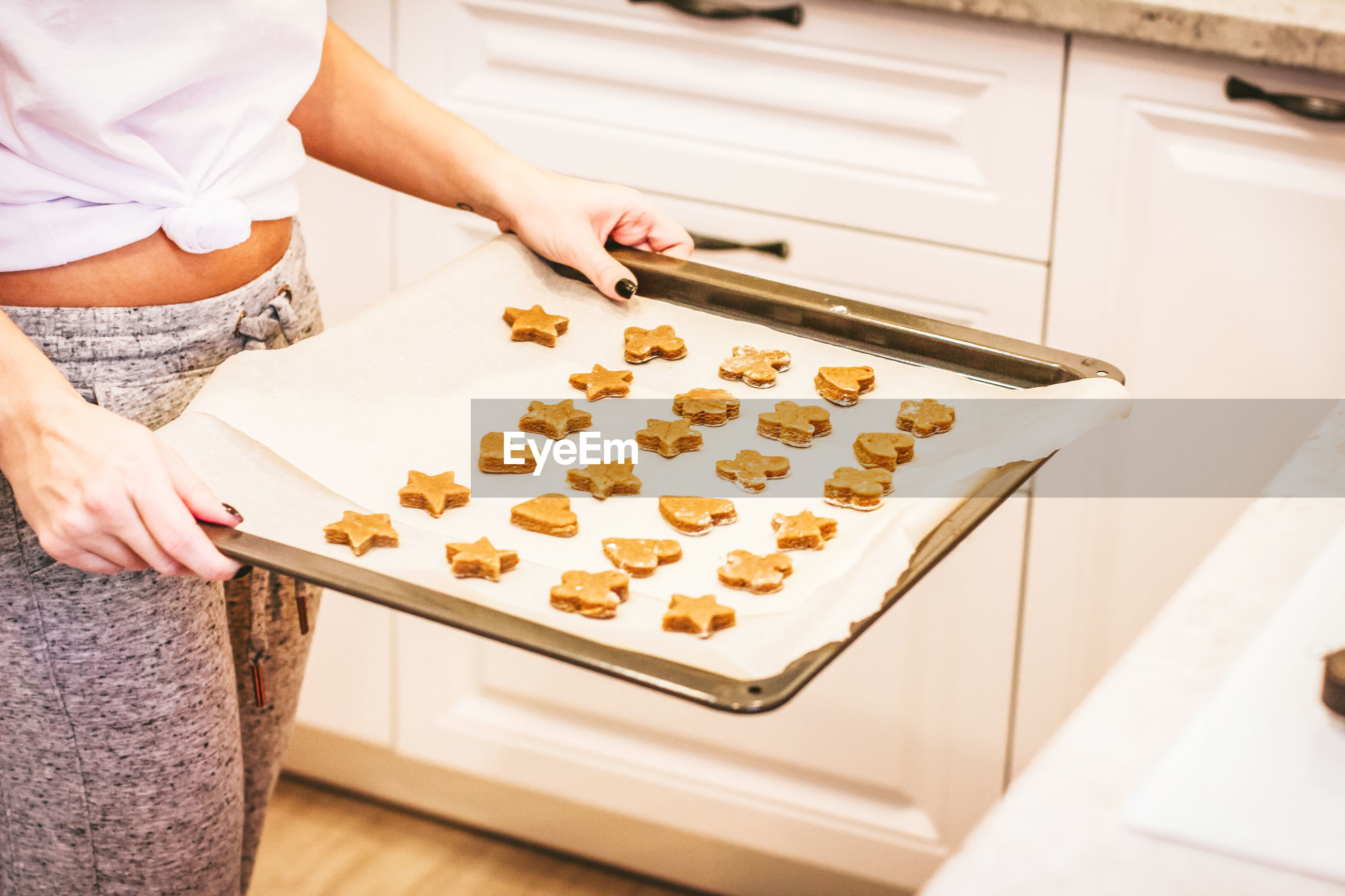 Midsection of woman preparing cookies in kitchen