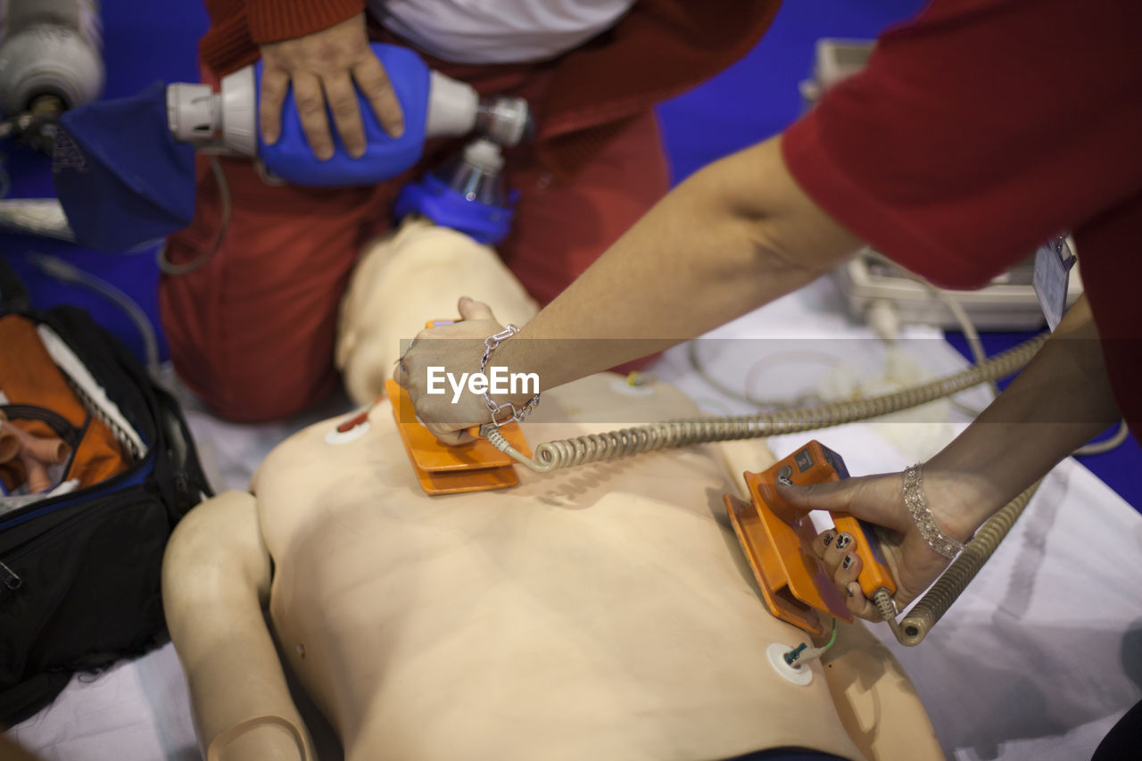 High angle view of doctors practicing with cpr dummy at hospital
