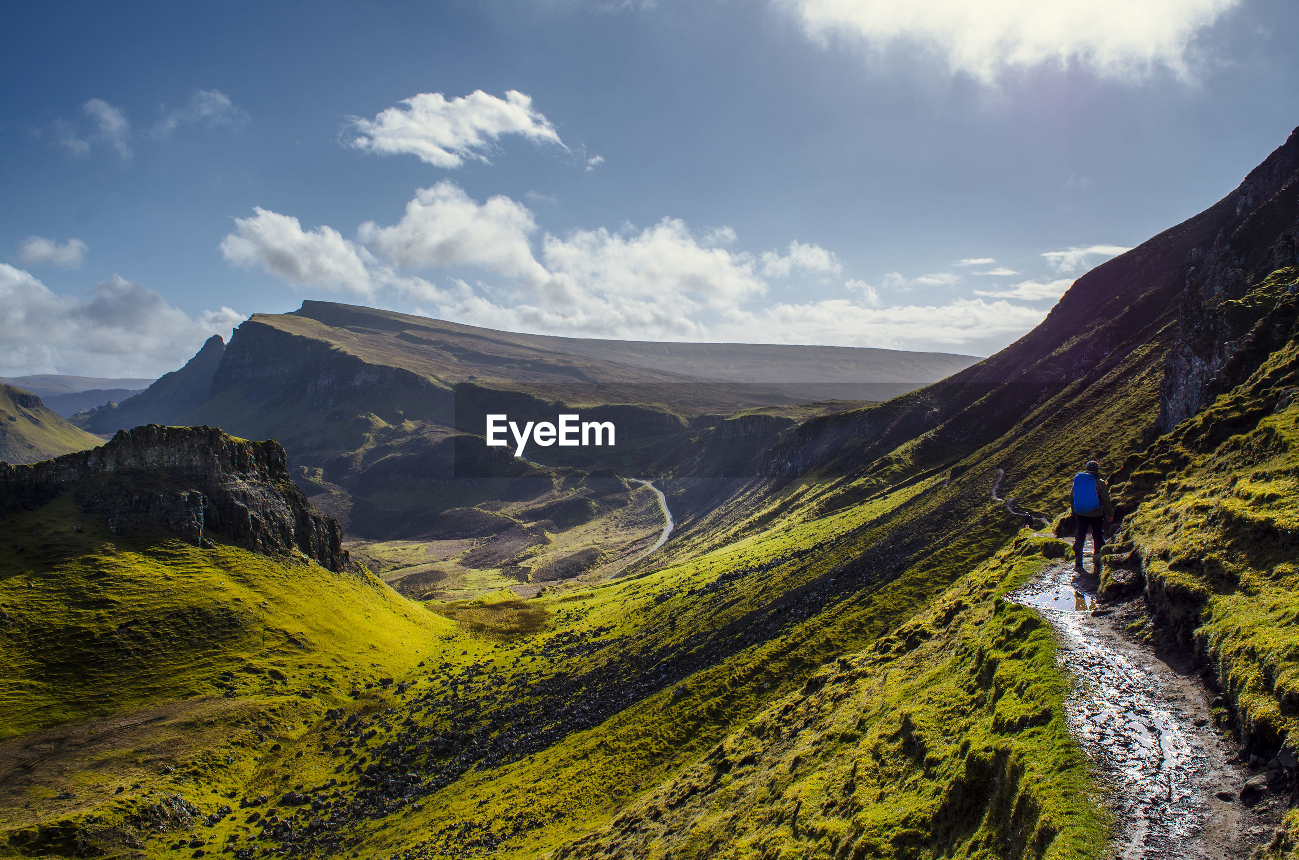 Man walking on mountain against cloudy sky