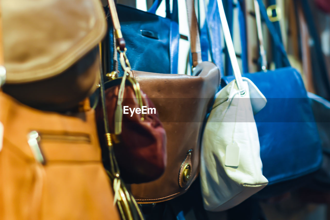 focus on foreground, close-up, clothing, day, bag, holding, musical instrument, real people, blue, hanging, music, one person, selective focus, outdoors, unrecognizable person, arts culture and entertainment, metal
