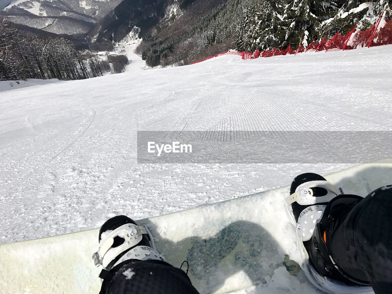 Low section of person snowboarding downhill on mountain