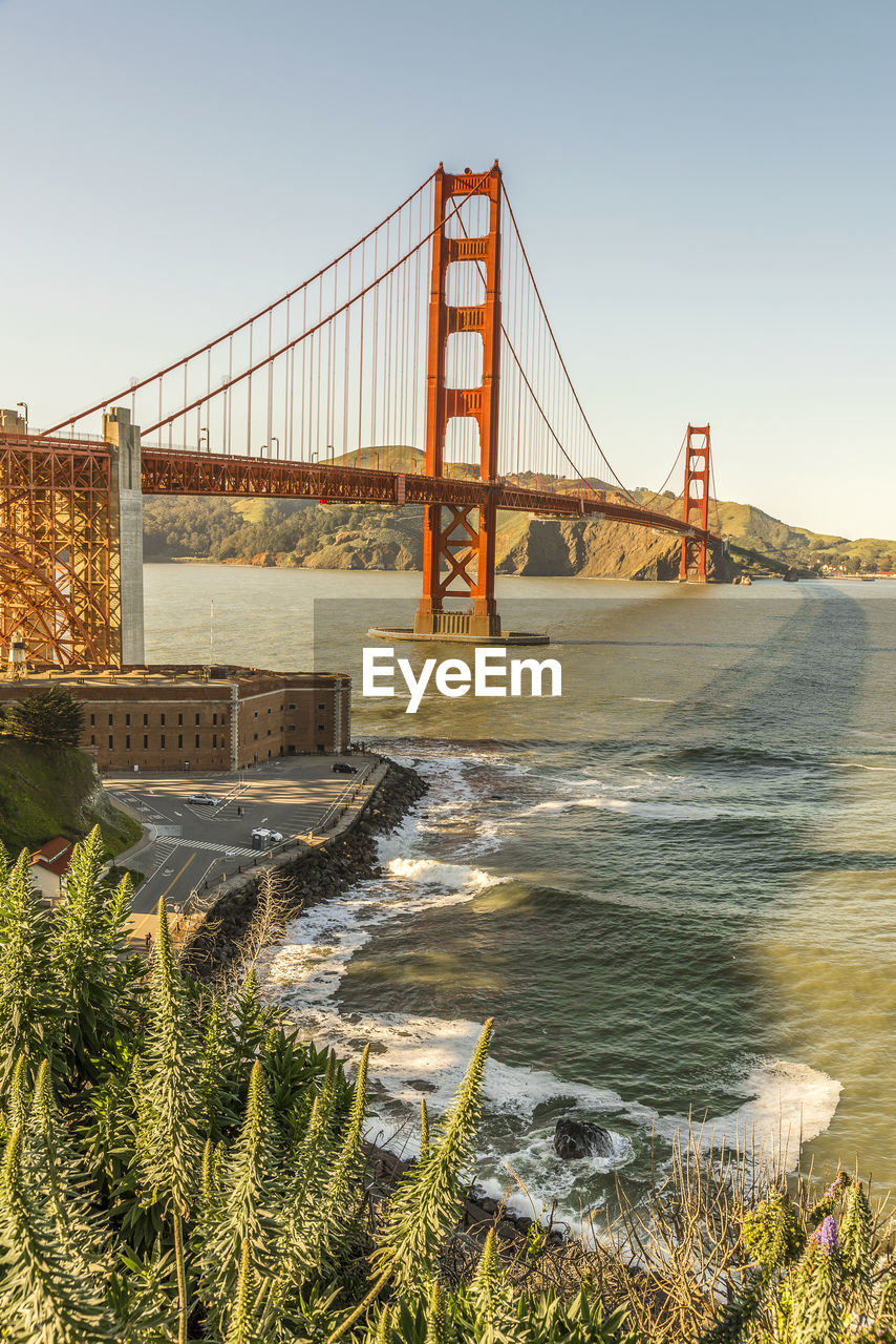 water, bridge, bridge - man made structure, connection, built structure, architecture, travel destinations, nature, sky, suspension bridge, transportation, tourism, travel, no people, sea, bay of water, clear sky, bay, outdoors