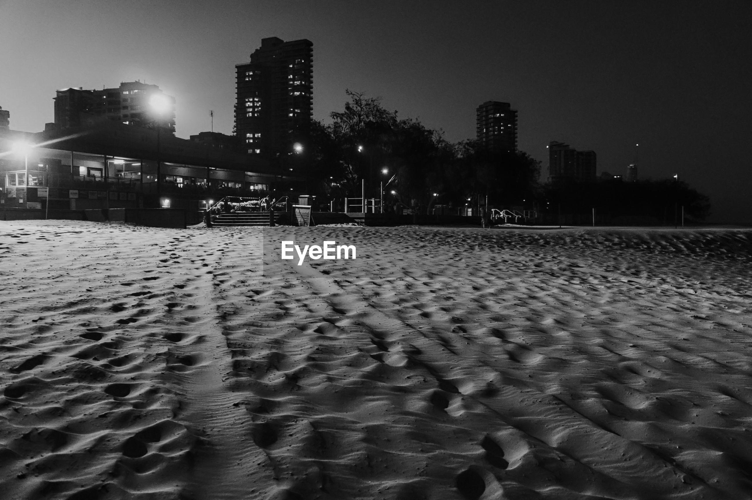 Sandy beach against buildings in city