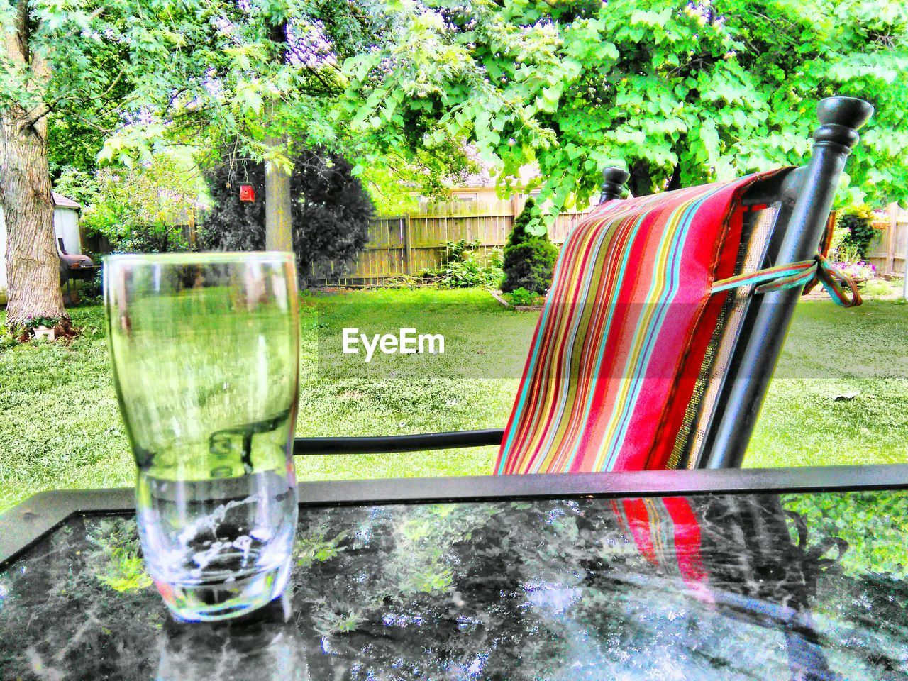 Close-up of drink on table by chair at yard