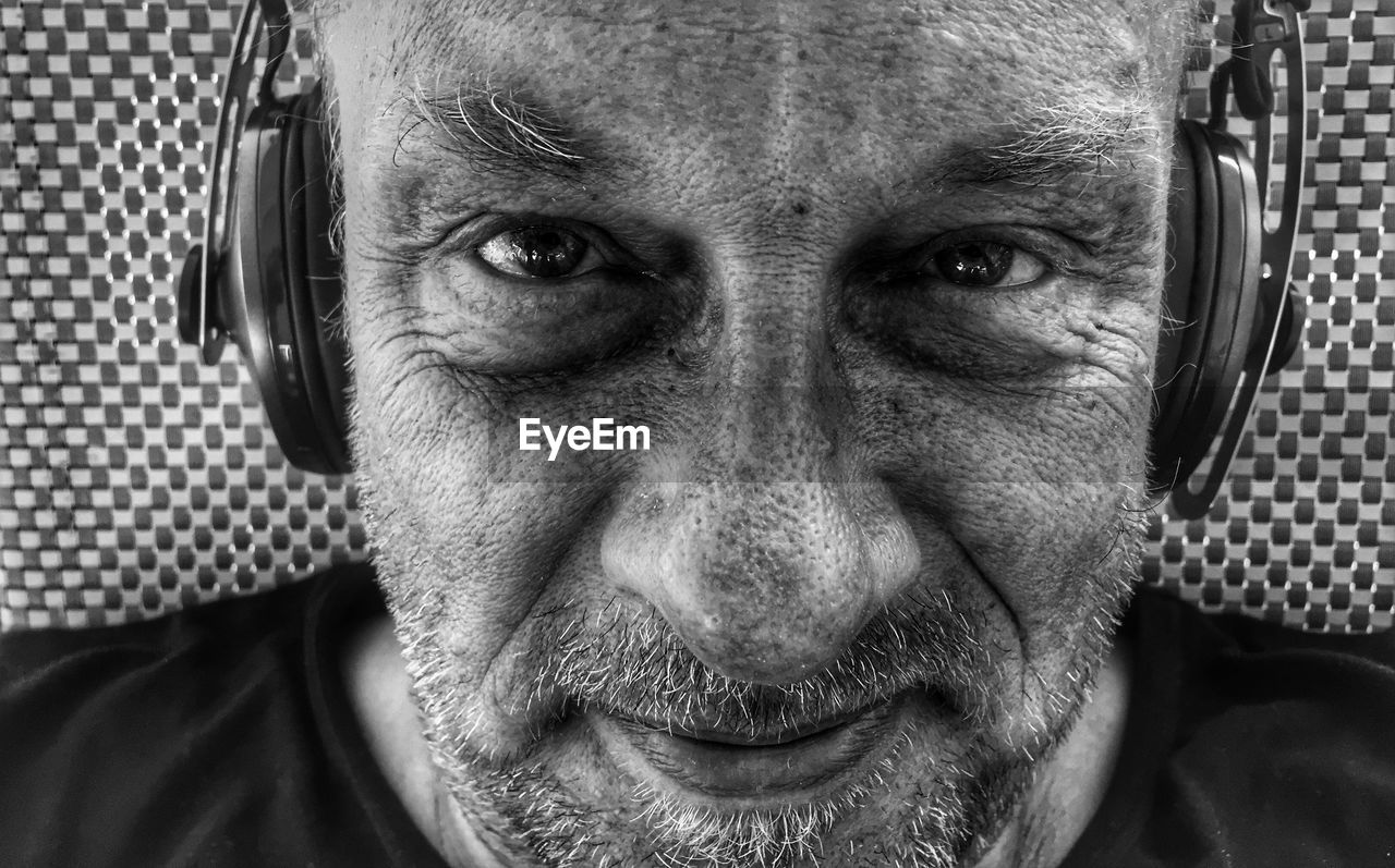 Close-Up Portrait Of Man Wearing Headphones By Wall