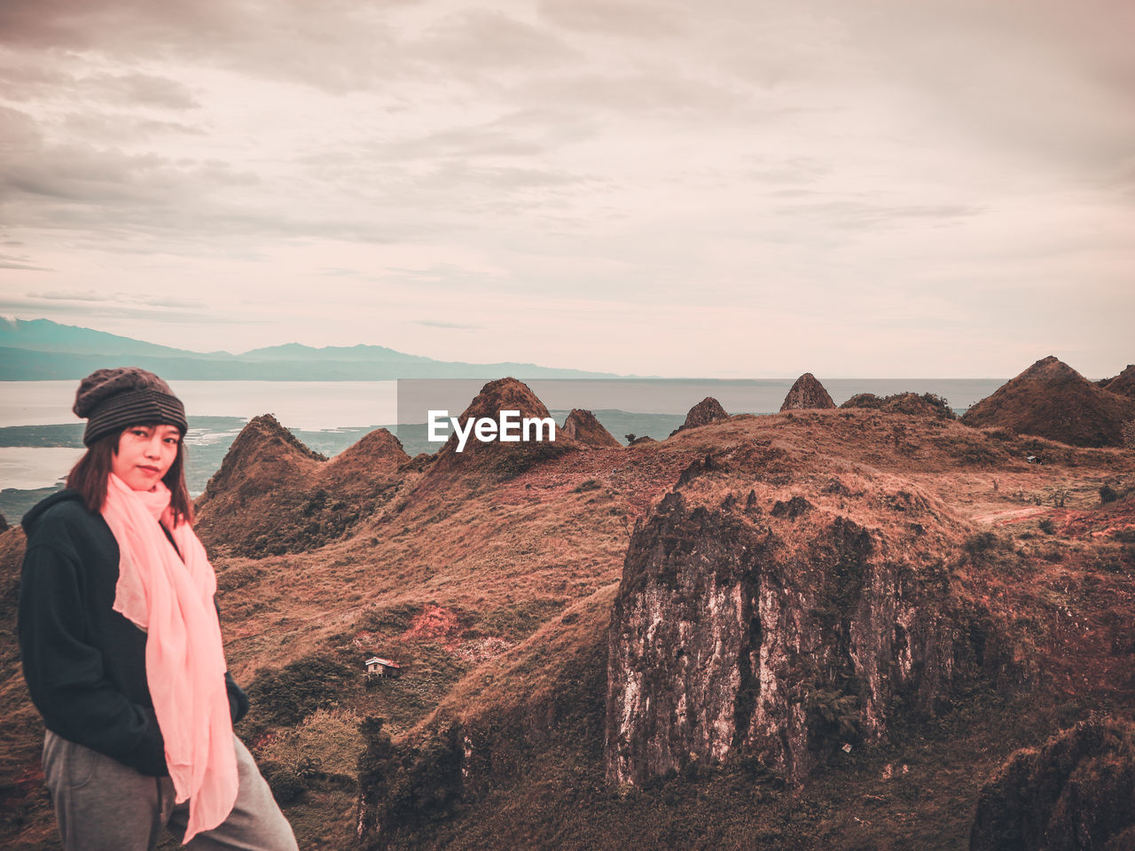Young Woman Standing On Rock Formation Against Sky