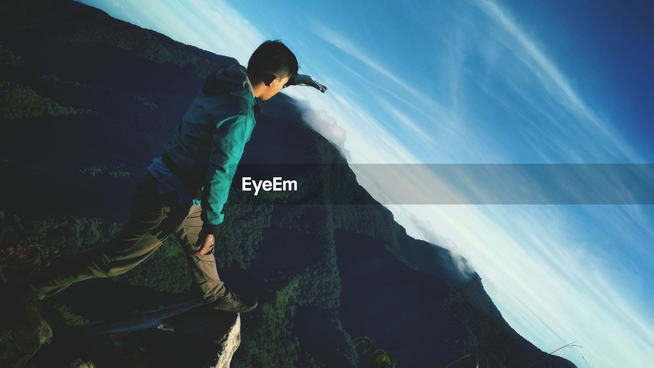Tilt shot of man on mountain against blue sky