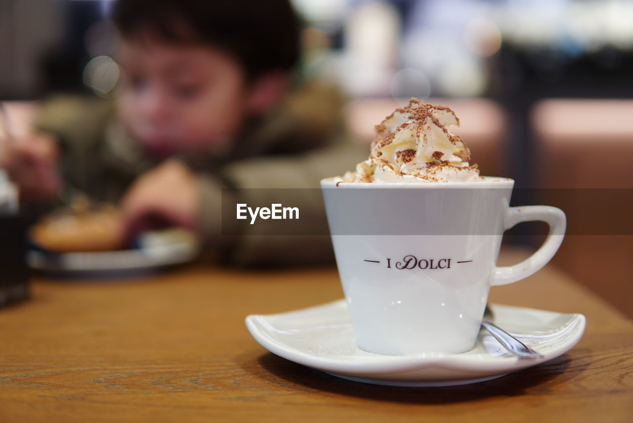 food and drink, cup, food, table, coffee, coffee cup, indulgence, drink, mug, refreshment, sweet, coffee - drink, freshness, focus on foreground, sweet food, spoon, kitchen utensil, crockery, indoors, temptation, saucer, hot drink