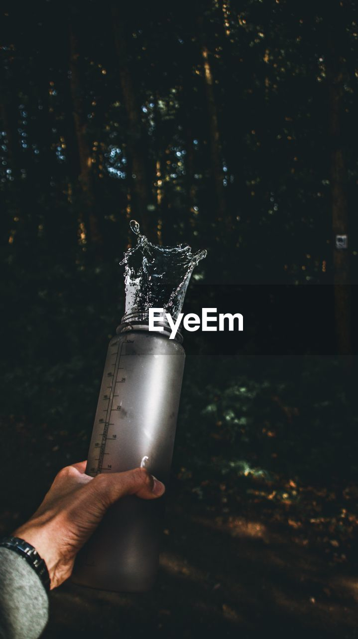 Cropped Hand Holding Water Bottle At Forest
