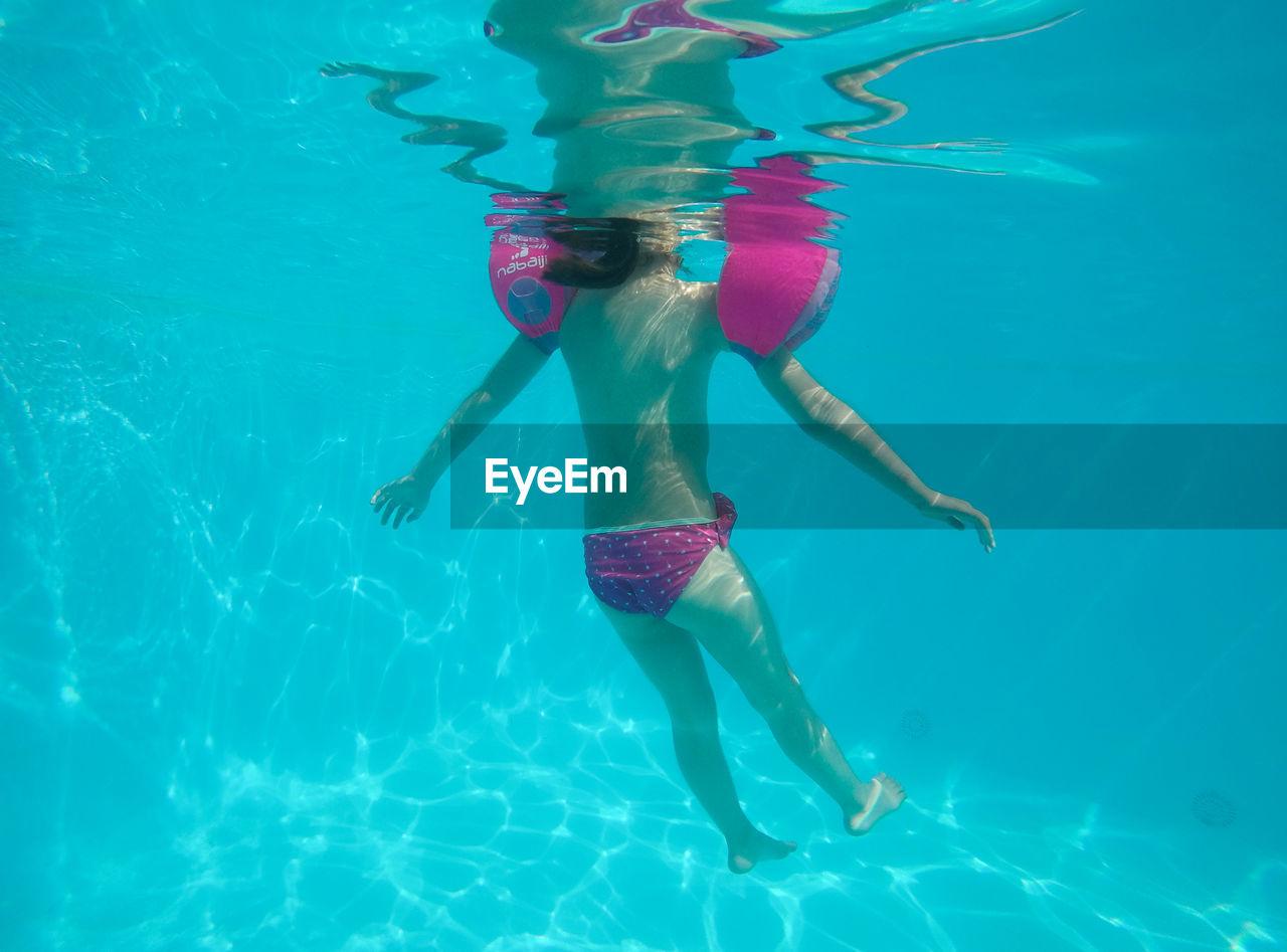 Girl Swimming In Swimming Pool